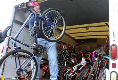Todd Jones, secretary of Bikes for Kids, helps load up the trucks with bicycles of all colors and makes, headed for Long Island. (Photo by L.E. Agnelli)