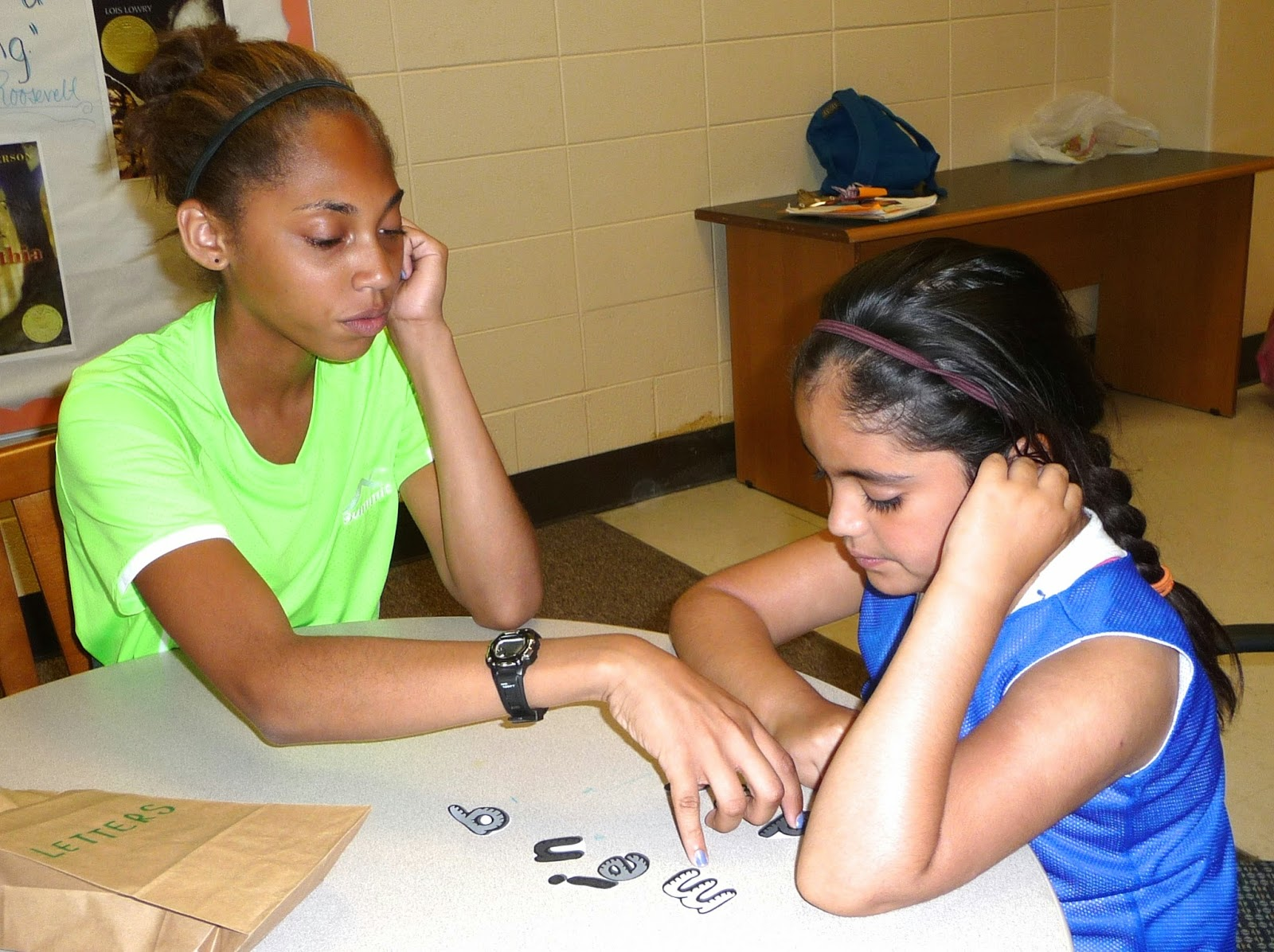 Lauren, a Junior Counselor, helps a girl on her team during reading class