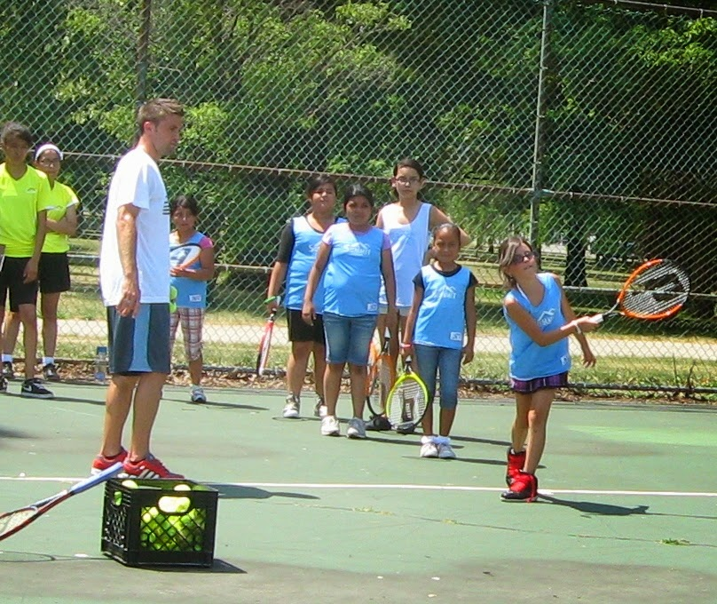Tim instructs the Summit girls on Tennis skills during the Summer Olympics Program.