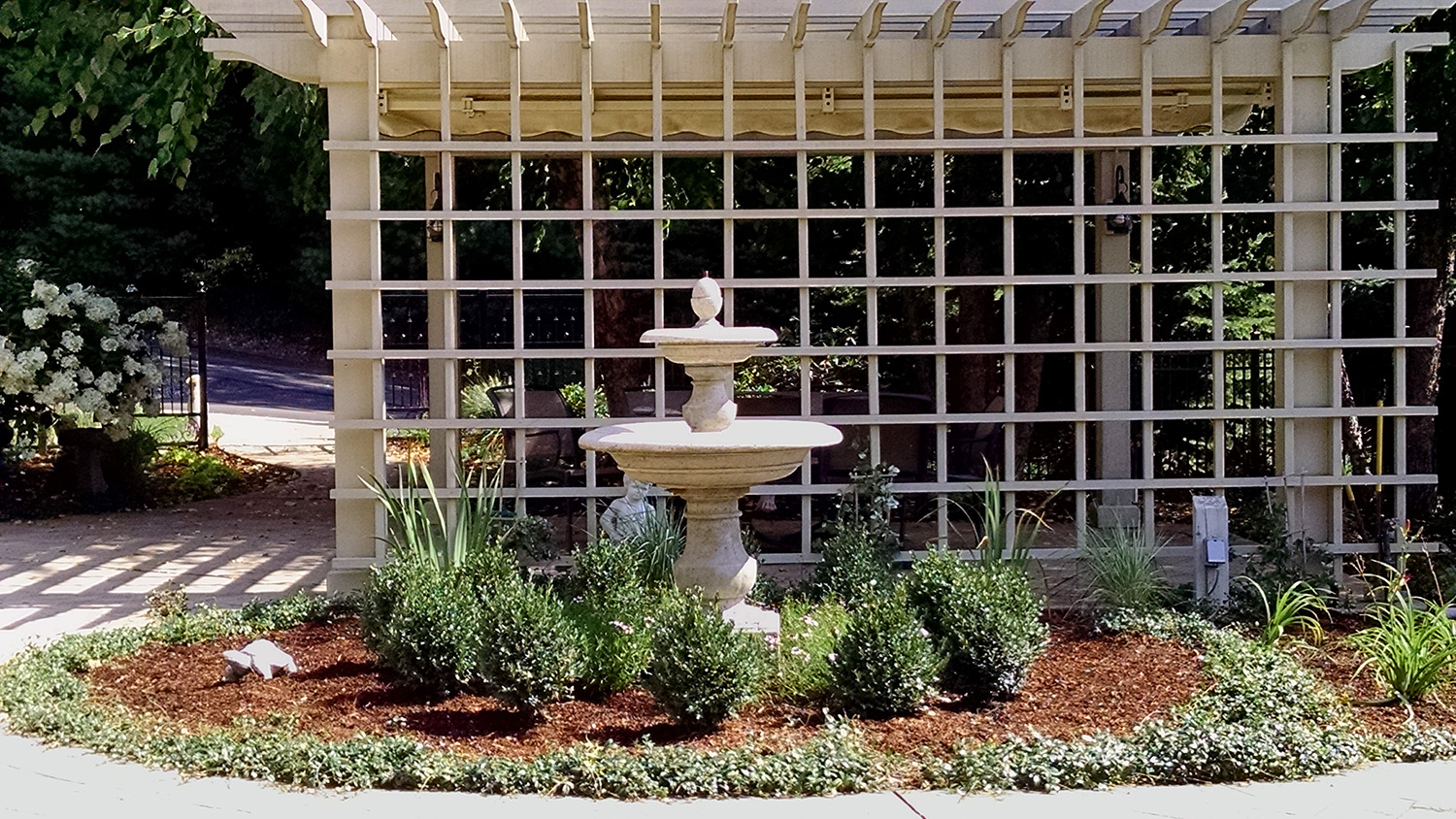boxwood surrounds 2-tier water fountain in formal garden