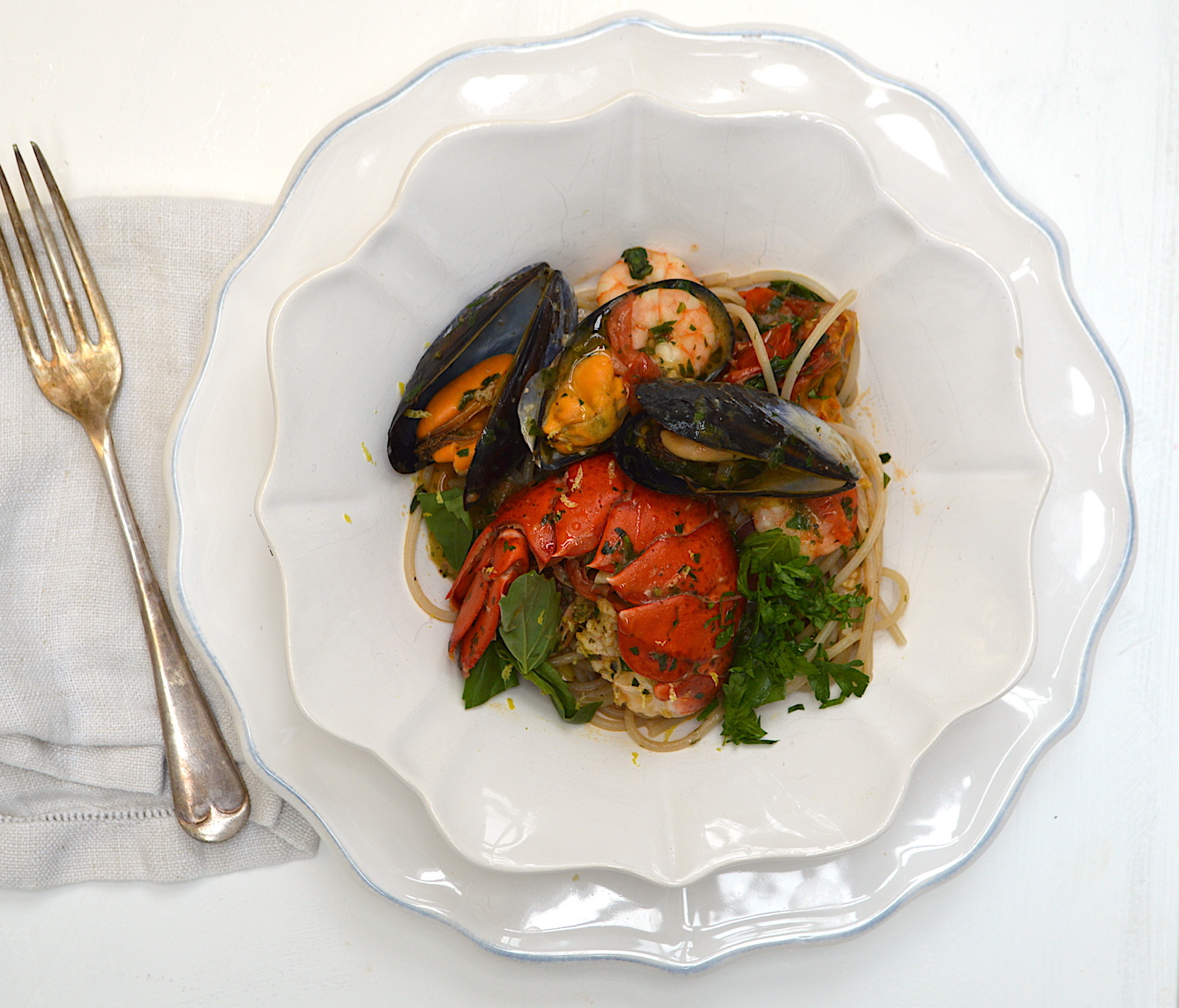 I made this recently for the amazing Laura Fantucci from  Wardrobe Icons for a summer dinner party. She requested this recipe which mainly originates from Campania and uses lots of crustaceans with scoglio meaning rock. Laura wanted to throw some lobster into the mix which adds another depth of flavour from their shells but you don't have to if you want to keep costs down. If not using you can just swap the lobby for more shellfish. There is something so rustic and beautiful about this dish that can't fail to whisk you off to the Italian Riviera. Make sure you throw on some jazz while you're cooking!  Serves 2  Ingredients:  160g dried linguine pasta / gluten free is good too!  275g baby plum tomatoes, halved  2 large garlic cloves, diced  1 banana shallot, diced  150g king prawns (shell on or off)  3 tbsp chopped flat leaf parsley  1 tsp dried oregano  large handful fresh basil, roughly torn  3 tbsp extra virgin olive oil  2 handfuls mussels  2 handful clams  1 lobster tail, sliced in half  5-6 tbsp hot vegetable stock  1/2 glass dry white wine  sea salt and black pepper  zest and juice of half a lemon  Prepare everything before you start to cook to make the whole process run smoothly. Set a large saucepan of salted water to boil and set a frying pan with a lid to a medium to high heat. When the water is boiling add the pasta to cook following the packets instructions and make sure you set a timer to keep track. For perfectly al dente I always take off about two minutes from what the packet says.  While the pasta is cooking you need to start on the sauce. Add the olive oil into the frying pan followed by the diced shallot. Let this soften for 2 minutes before adding in the garlic followed by the plum tomatoes. Stir everything around the pan for two minutes and then add half the parsley, oregano, lobster tail, clams, mussels and white wine. Turn up the heat and allow this to cook for 1 minute and then pour over the stock and cover the pan with the lid. Cook for 2 mi