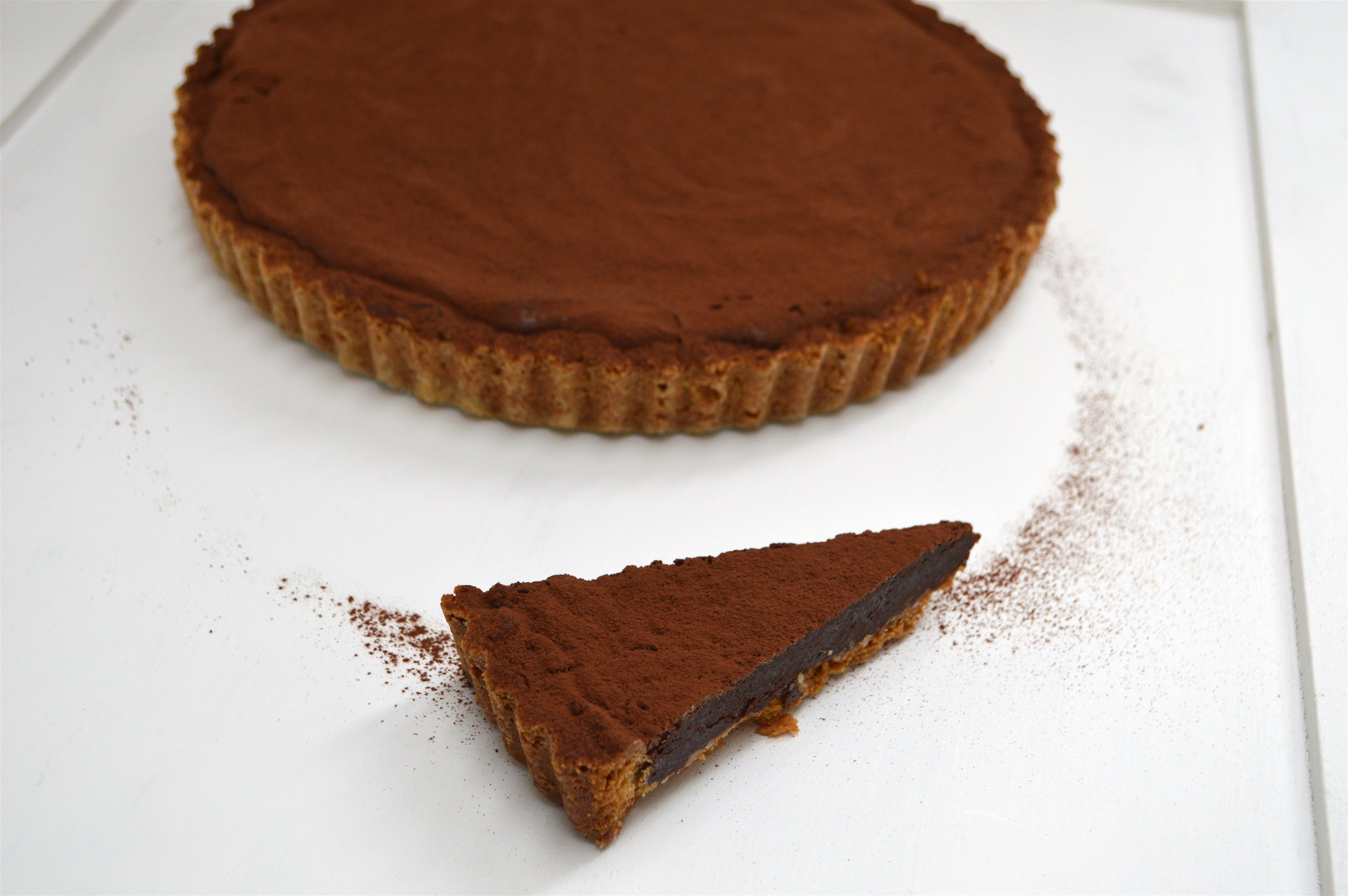 I made this for my sister's birthday popup dinner this week and is went down a storm. It has a wonderfully velvety smooth and rich filling with a flavourful, light pastry. It's actually quite simple to make as tarts go because there are only two stages but you must make sure you use a good quality chocolate. The main ingredient is choccy, so trust me, it has to be a good one. I recommend Lindt 70% coco for a good main stream one.  Serves 12  Ingredients:  For the pastry  230g spelt flour  100g almond flour/ground almonds  180g unsalted cold butter, diced  110g unrefined caster sugar  2 tsp vanilla extract  1 medium egg yolk  Pinch of sea salt  For the filling  5 medium eggs (4 yolks and 1 whole egg - lightly beaten)  300g dark chocolate, broken into pieces  135g unsalted soft butter  3 tsp vanilla extract or seeds from 1 vanilla pod  1 tsp instant coffee  140g unrefined caster sugar  100ml maple syrup  Coco powder for dusting  Start by making the pastry and add the spelt, almond flour, salt and sugar to a blender and pulse blend to mix it. Then add in the diced butter and blend. The mix should start to come together and after a couple of minutes add in the vanilla and egg yolk. Continue blending until the pastry comes together into a ball and wrap in cling film to rest in the fridge for at least one hour or overnight.  Preheat the oven to 170 degrees on the fan setting. Use a brush to evenly grease a loose bottom tart tray (23cm) and then dust gently with spelt flour so that it is lightly coated. Place into the fridge to keep cool. Get the chilled pastry and use a grater on the larger seating and start to grate the pastry. I like to do this instead over rolling so that you end up handling the pastry as little as possible. You want to try and keep it cool at all times. Get the pastry tin and begin fitting the dough into the mould. I would make it around 1-1.5cm think and this pastry is quite delicate so it doesn't matter if its a touch thicker that a normal wheat pas