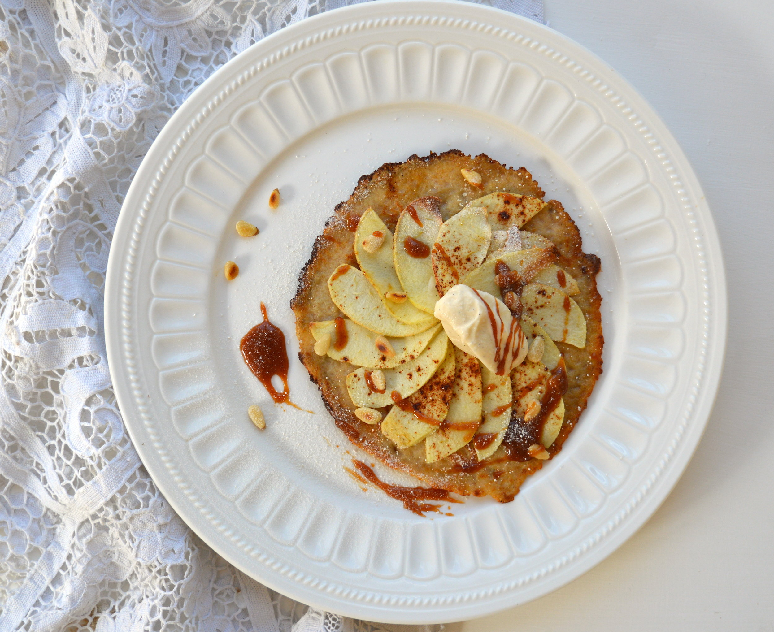 This is inspired by a wonderful apple tart that I had at L'Auberge De La Mole back in the summer in St Tropez. I have since dreamt of this delicate, beautiful tart that had a super-fine pancake-like base. It was so simple but really hit the nail on the spot! Here I have tried to recreate it from memory and I have added in a salted caramel sauce with a few crunchy pine nuts for good measure. This is a great dinner party dessert as it can be made ahead of time and thrown together just before serving.  Makes 4 tarts Ingredients: For the spelt crepe: 200g spelt flour 3 tbsp almond flour 500ml whole milk 1 tbsp unrefined caster sugar 1 tsp vanilla extract 2 medium free-range eggs 30g butter and extra sugar for frying  For the apples: 6 medium cooking apples, peeled 70-80g unrefined caster sugar 1-2 tsp cinnamon powder Zest of a lemon  For the salted caramel sauce: 150g unrefined caster sugar 150ml double cream pinch of sea salt  20g toasted pine nuts for garnishing Unrefined icing sugar for dusting Vanilla ice cream  Preheat the oven to 180 degrees on the fan setting.  Start by making the crepe batter. In a large bowl add the spelt, almond flour, sugar, vanilla extract and mix together. Make a well in the middle of the flour and add the eggs mixing together with a wooden spoon. Then slowly pour in a little milk into the centre and mix. Continue adding the milk and mixing careful to avoid lumps. You will need to beat it quite hard at the beginning and keep adding until all the milk is incorporated. Heat a large non-stick frying pan to a medium to high heat with a little butter and once hot spoon 1-2 tablespoons of the batter into the centre of the pan. Try to keep the pancake thin, small and round so avoid moving it around the pan too much. Just before you turn it over add a little more butter to the pan and a good pinch of sugar. Then use a spatula to flip it over trying to make sure some of the sugar gets underneath the pancake. This will caramelise and crisp up the bot