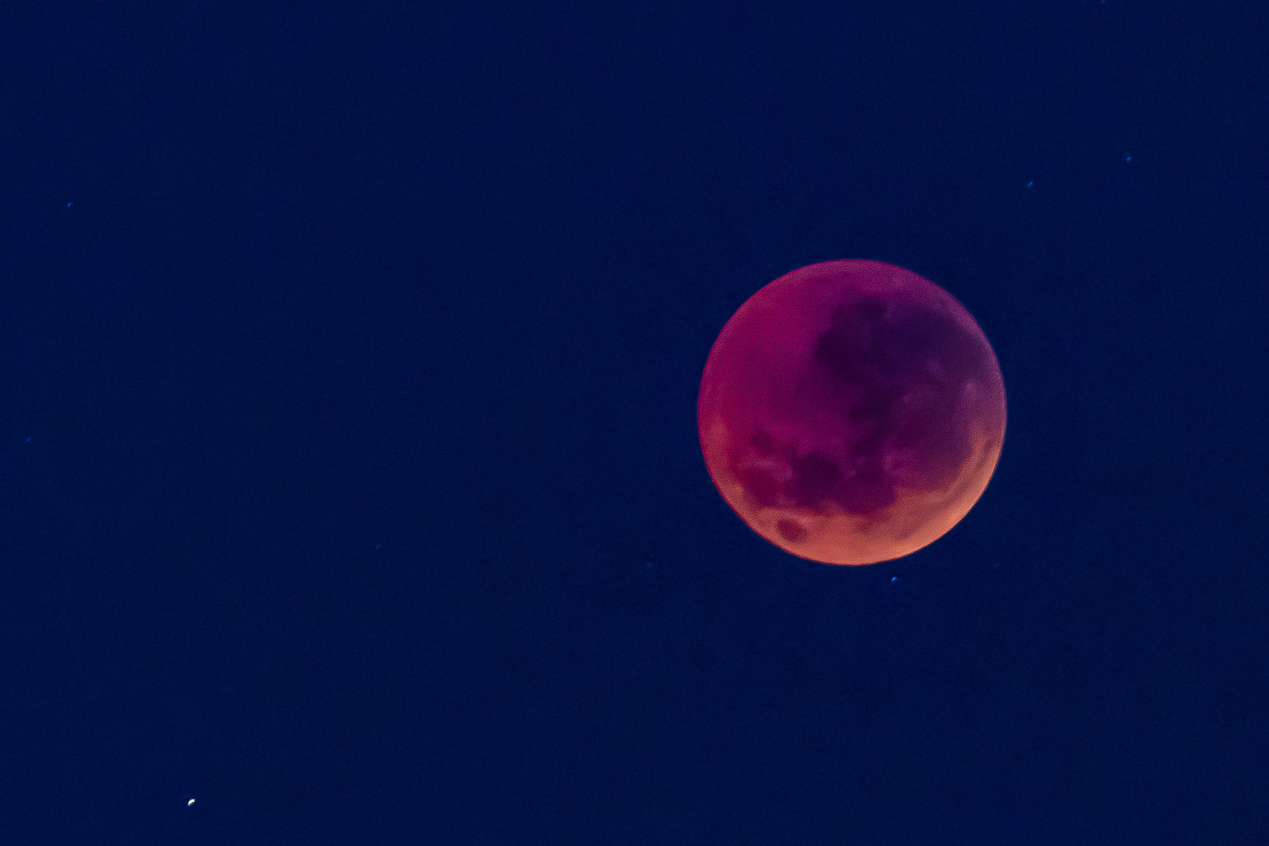…a blood moon which means that while the moon is in total shadow (blocked by both the sun and earth), the sun's light is passing through Earth and bending towards the moon making the moon appear to be blood red.