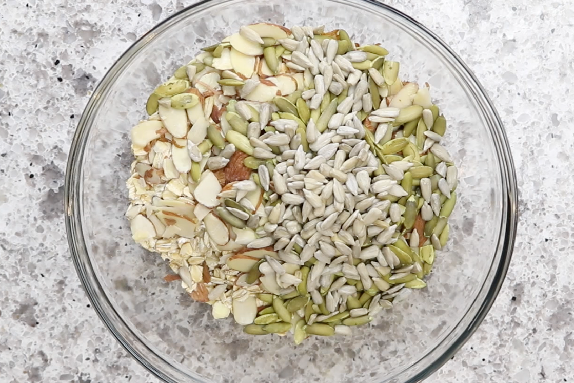 2. Combine oats, almonds, pumpkin seeds, sunflower seeds, flax seeds to a large mixing bowl. -