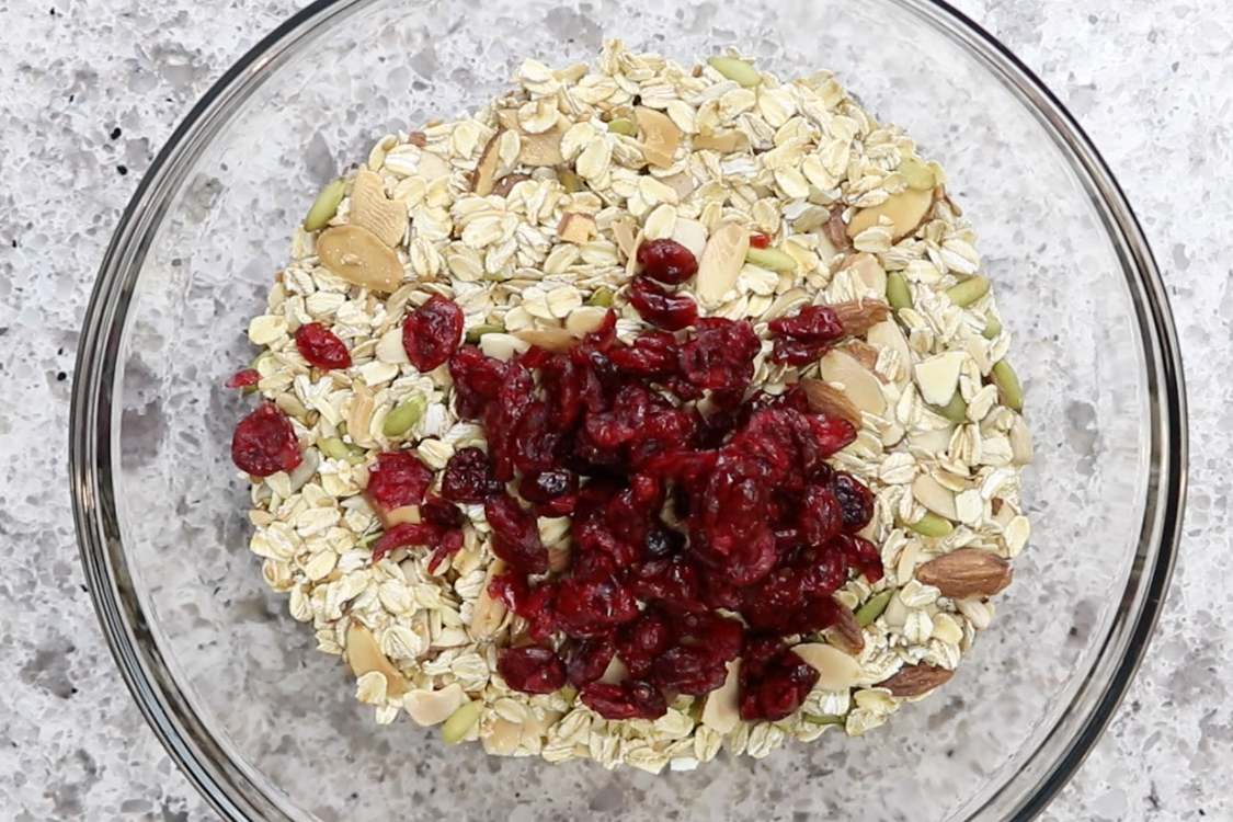 4. Remove baking pan from oven and transfer oat mixture to large mixing bowl. Add cranberries. -