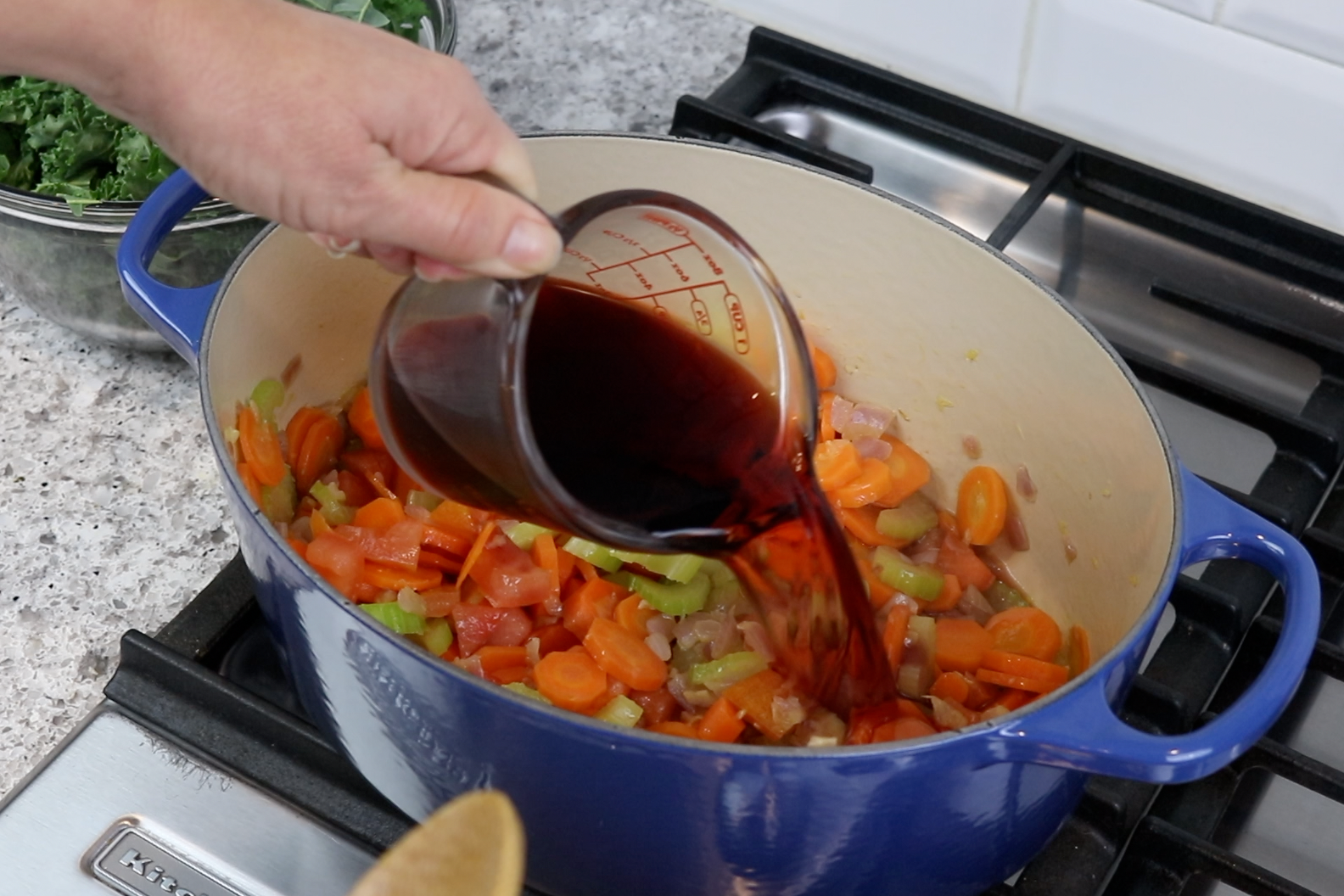 3. Stir in the garlic and cook for 3 minutes. Add the wine and tomato and bring to a boil. -