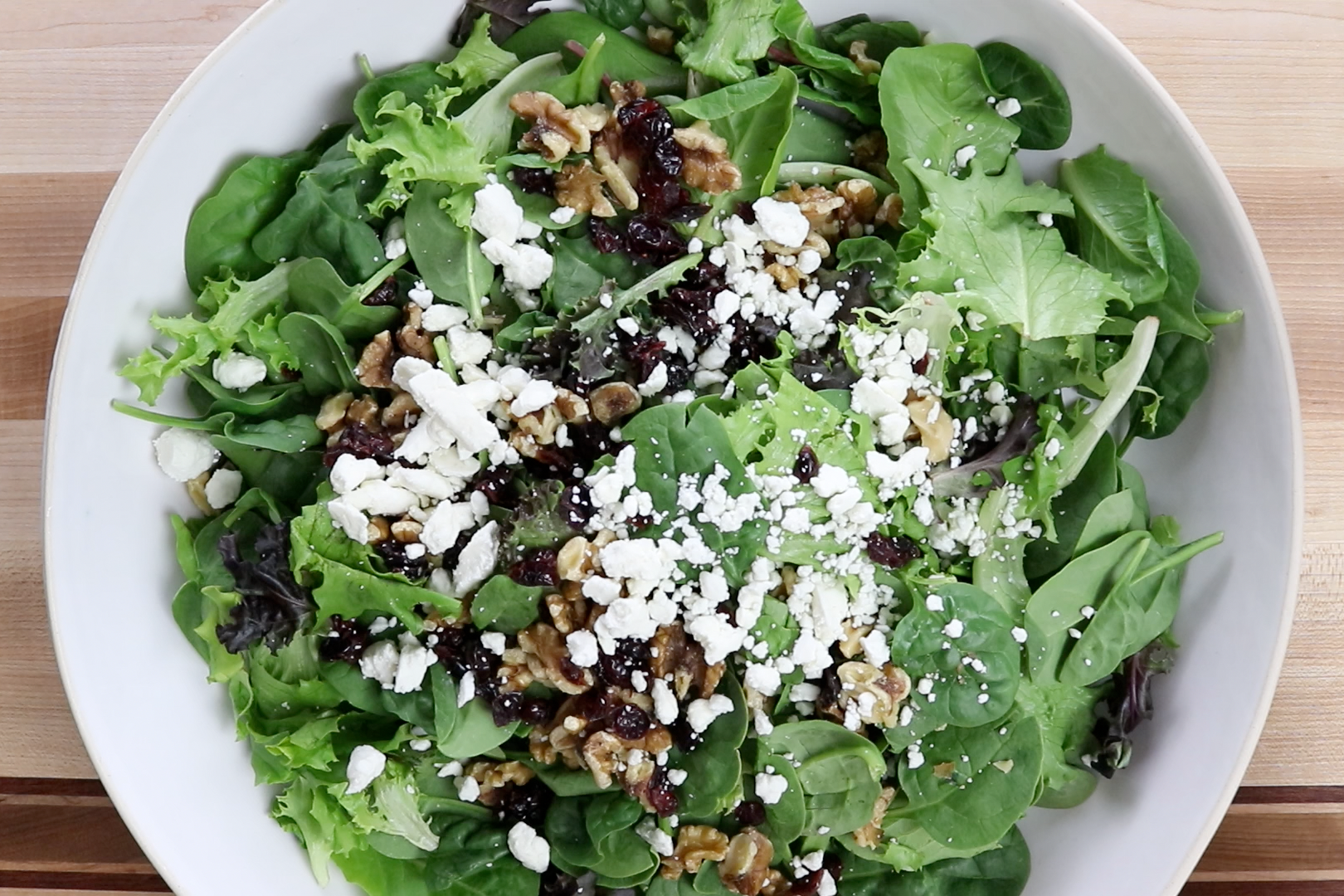 4. Toss lettuce, walnuts, cranberries, and feta together in a large bowl. -