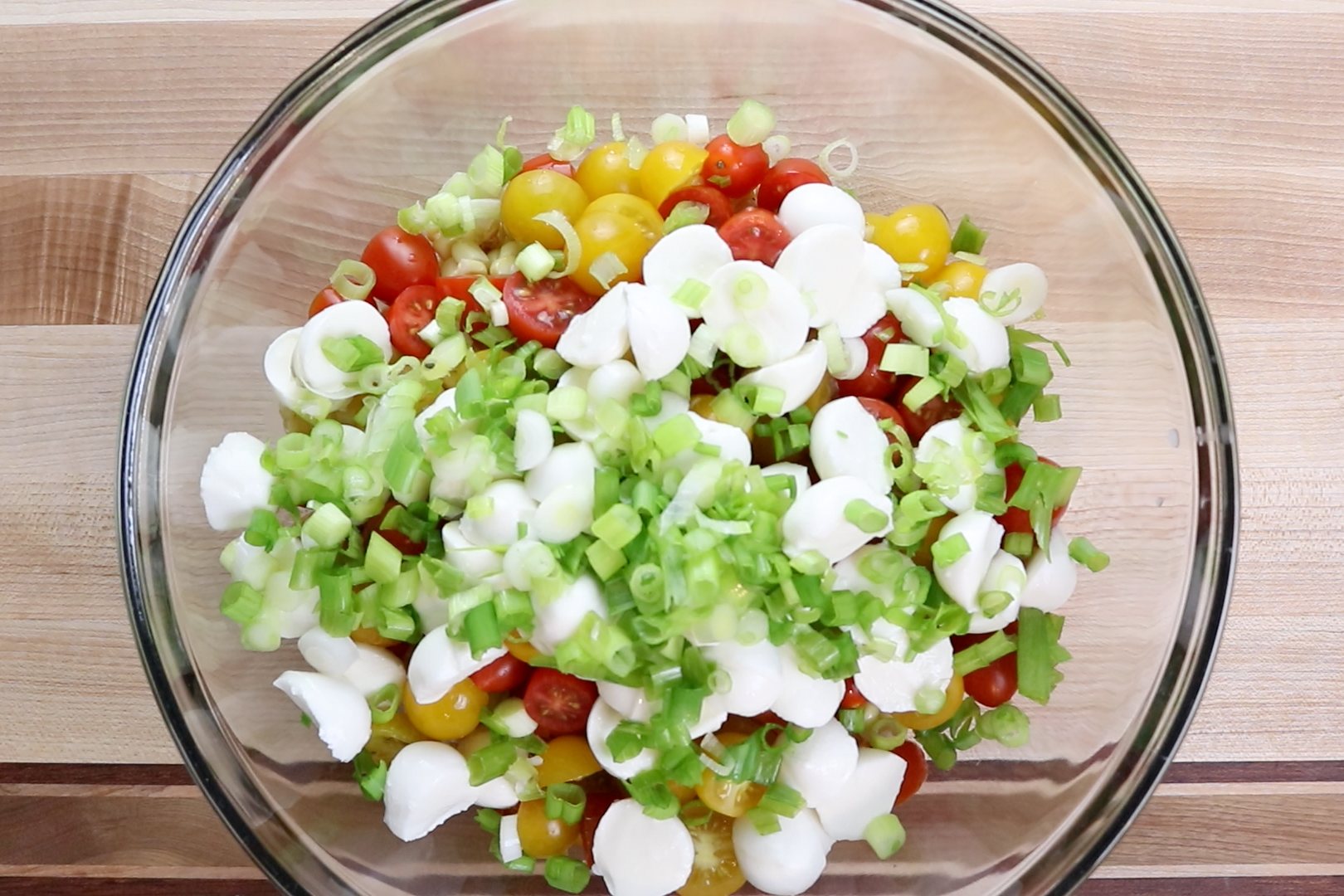 6. In a large bowl combine corn, tomatoes, mozzarella and green onions. -