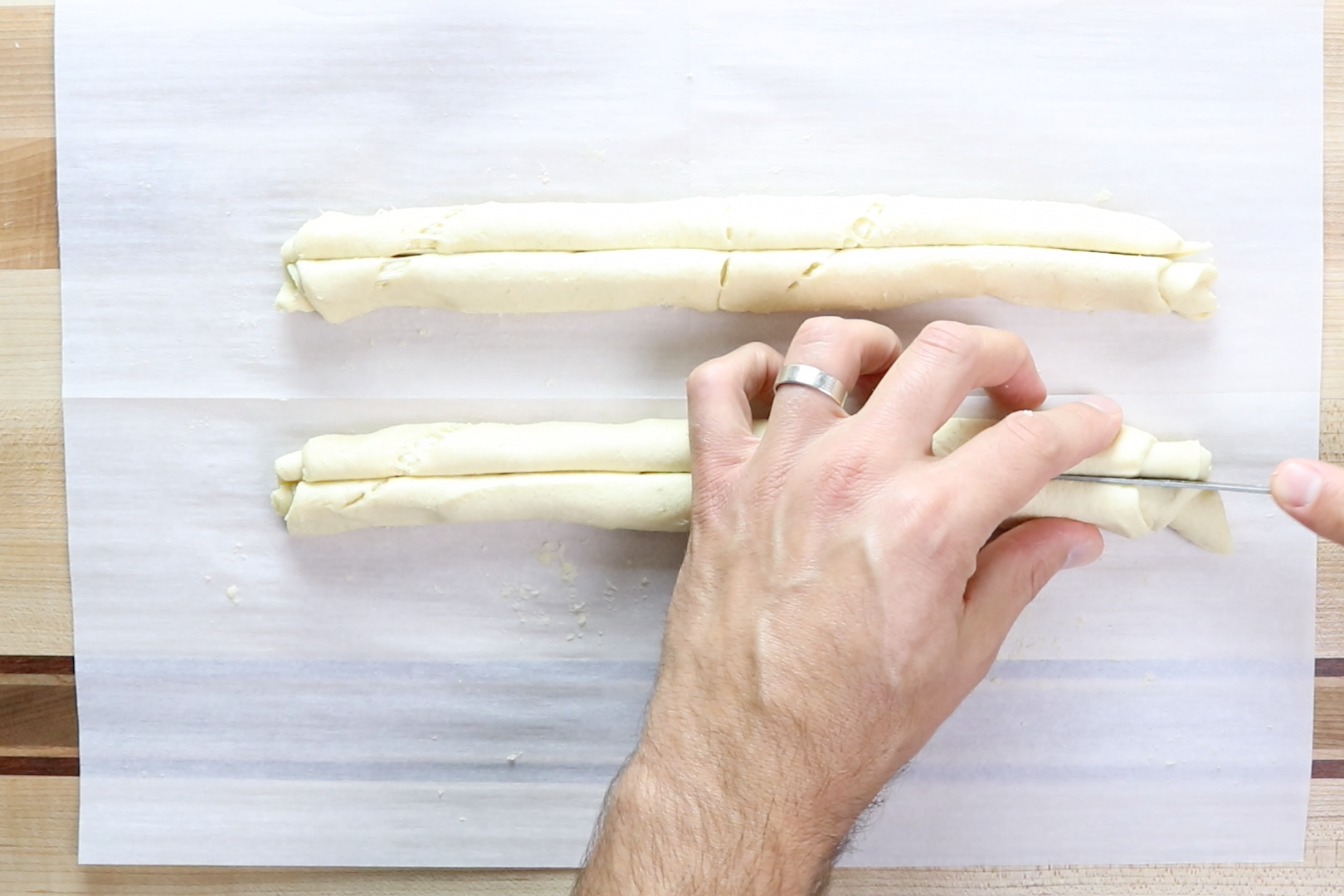 5. Then, cut each roll in half vertically down the center. Grab the ends of each piece of dough and gently pull them in opposite directions to stretch the dough a little. -