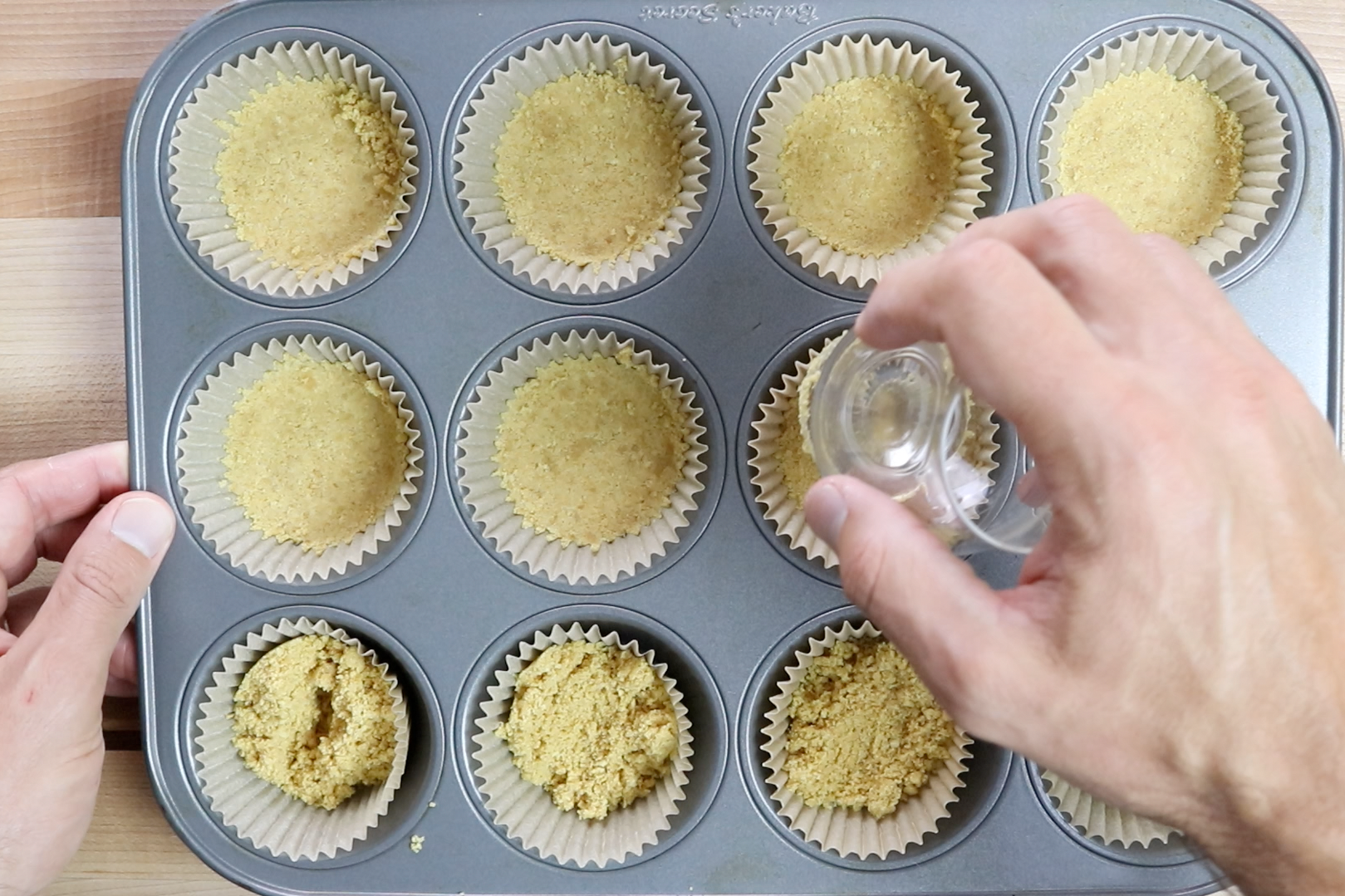 3. Spoon 1 tablespoon of crust into each cupcake liner. Press the graham cracker mixture into each lining with a spoon or the bottom of a glass. Bake for 5 minutes and set aside. -