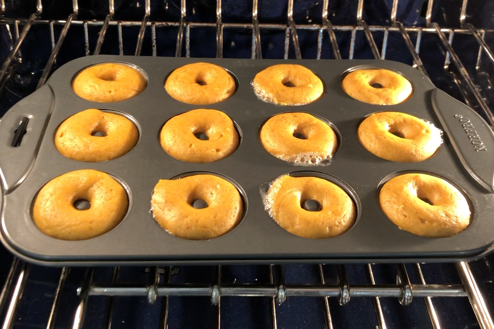 7. Bake for 13-15 minutes, until the donuts are lightly golden and spring back when touched. Let the donuts cool in the donut pan for about 5 minutes before transferring to cooling racks to cool. -