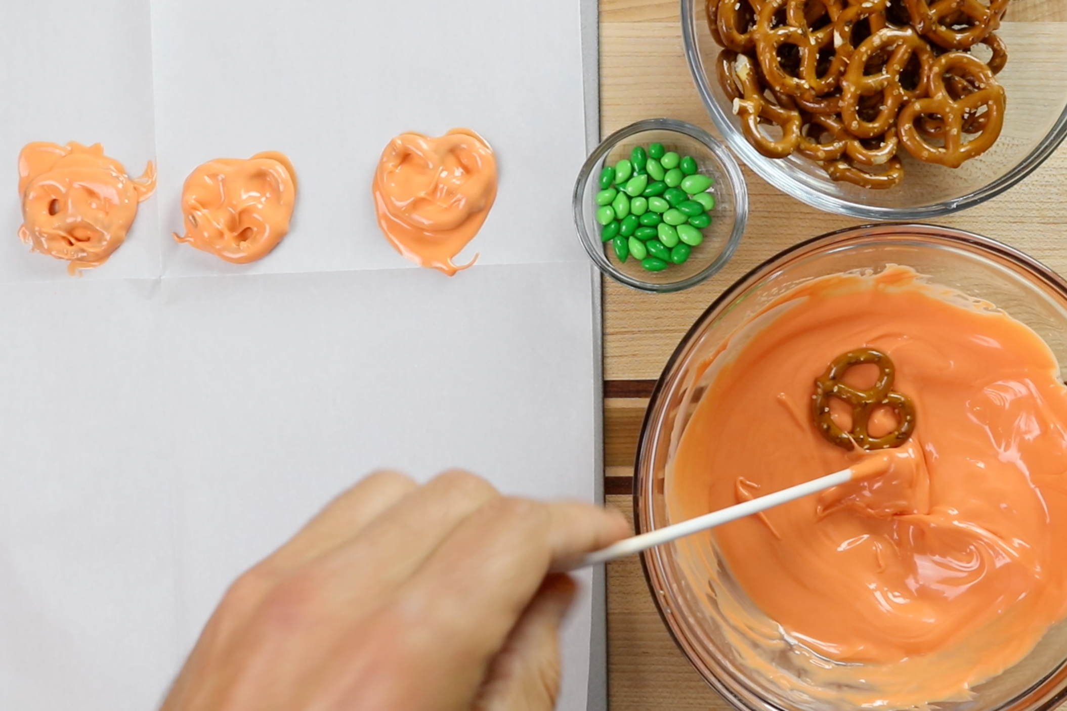 4. Drop the whole pretzel in the coating and submerge it slightly. Use a dowel or fork to pull the pretzel out of the melted mixture. Carefully place it on the prepared baking sheet. -
