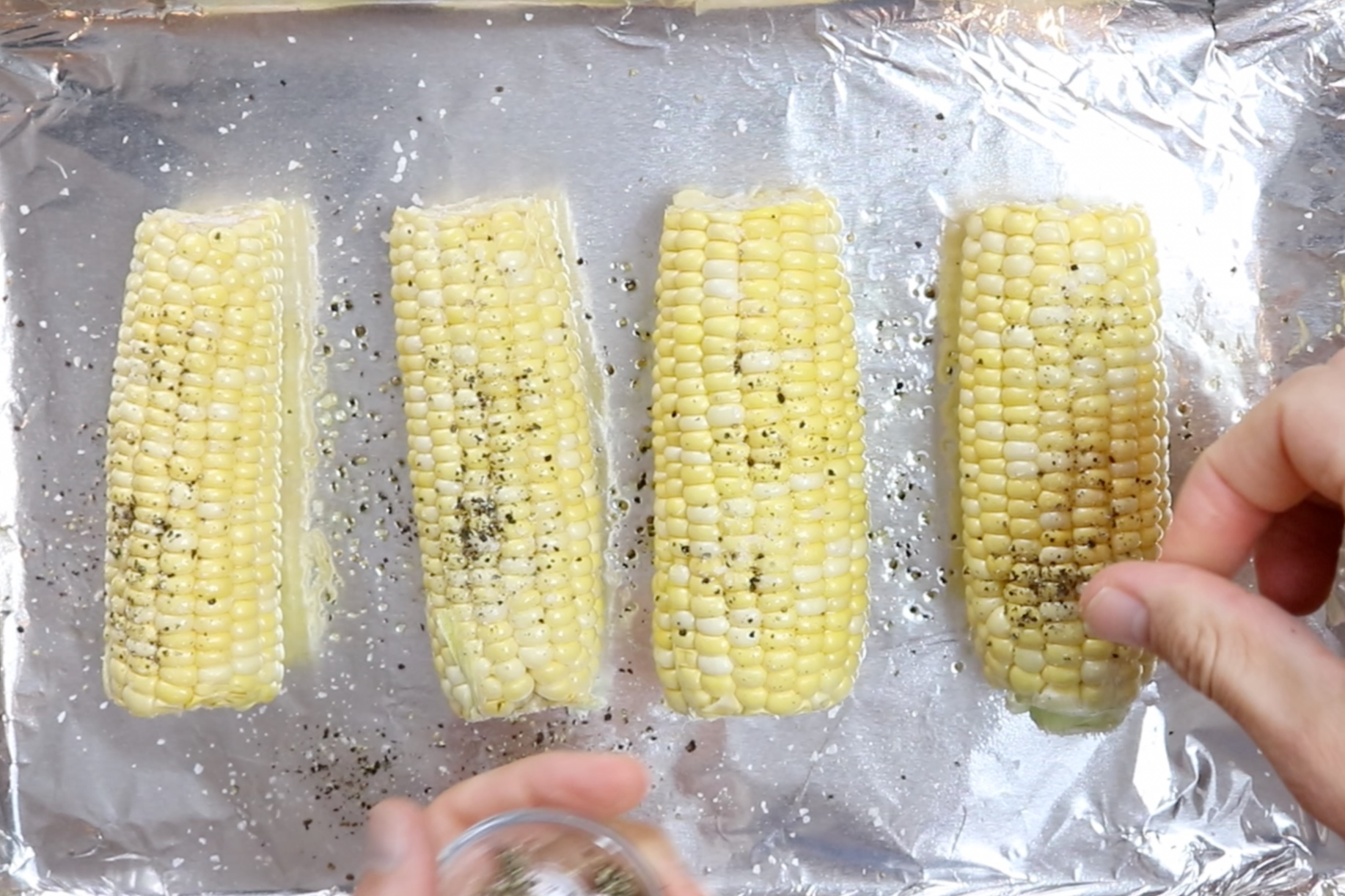 1. Heat the oven to 400°F. Prepare baking sheet with aluminum foil. Brush corn with olive oil and season with salt and pepper. -