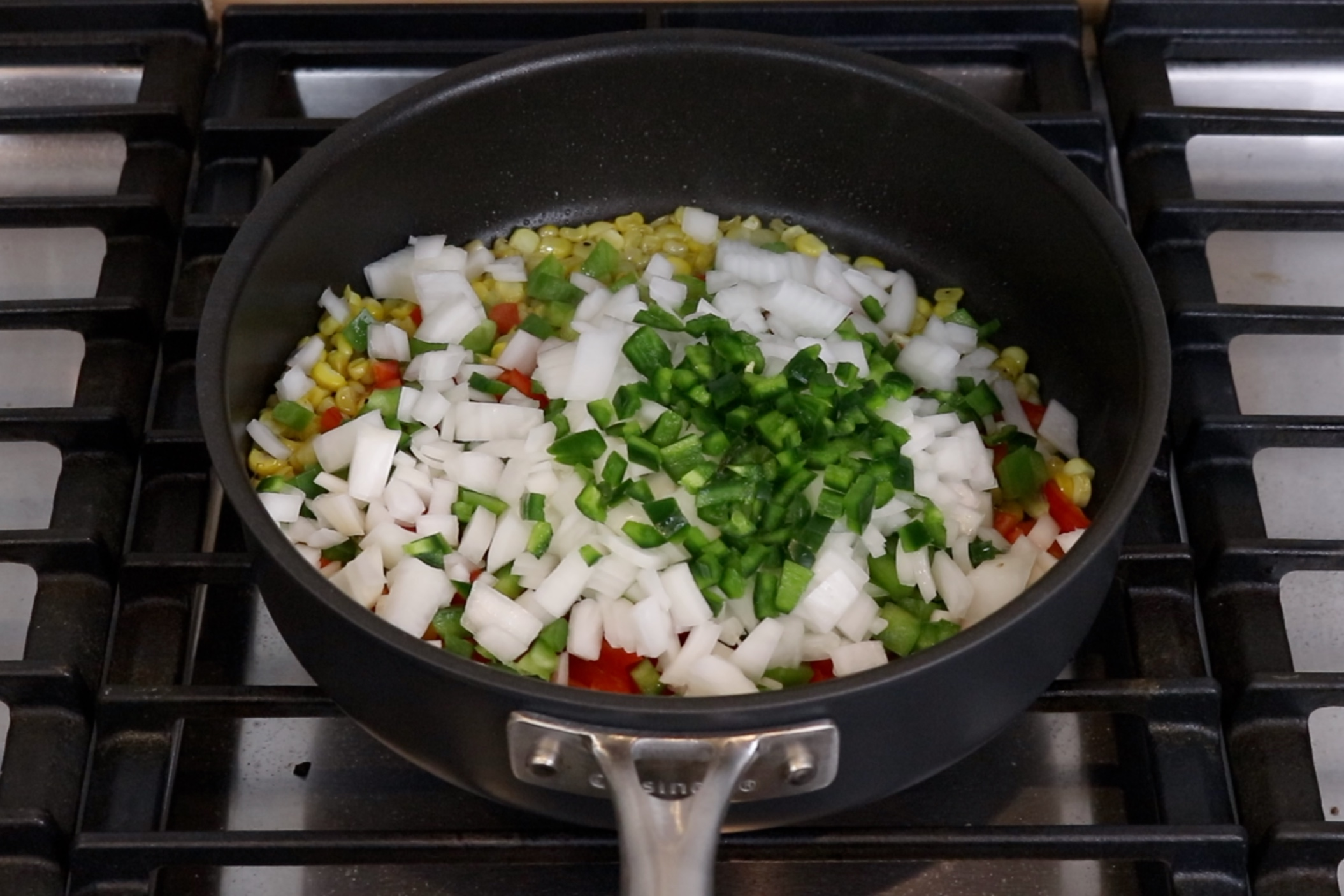 6. Add corn, onion, red and green bell pepper and jalapeño to the skillet. -