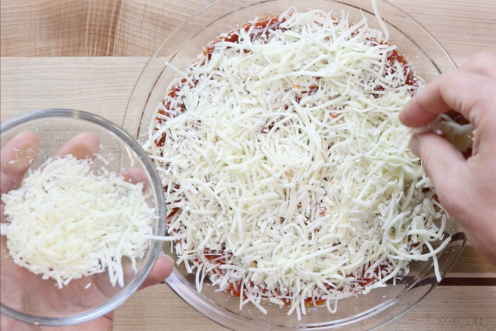5. Sprinkle the remaining Parmesan cheese over the sauce followed by the rest of the Mozzarella. -