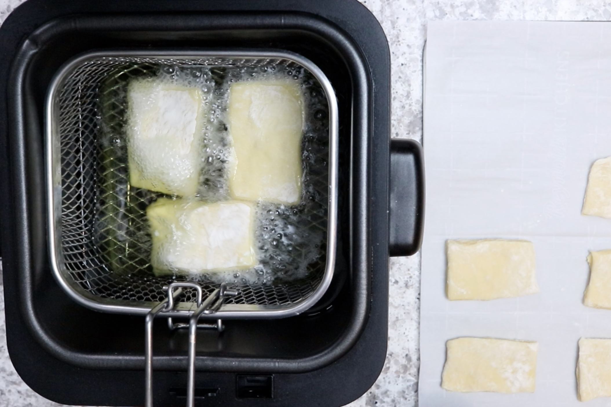 9. Drop a few dough squares into the hot canola oil and spoon oil over the top of each of them while cooking. -