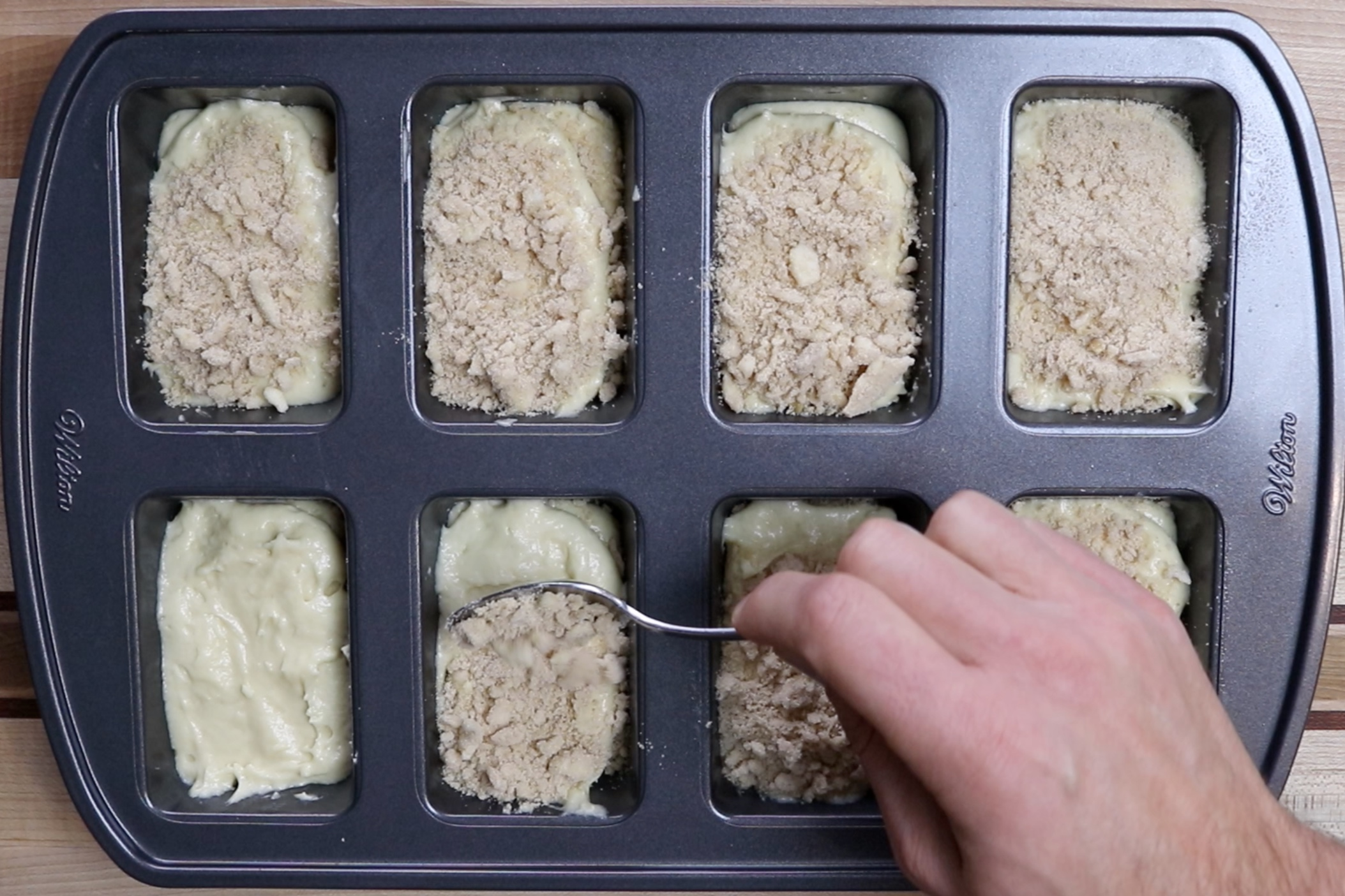 12. Spoon or pipe remaining mixture spreading evenly over the topping. Finish by sprinkling remaining topping over the loaves. -