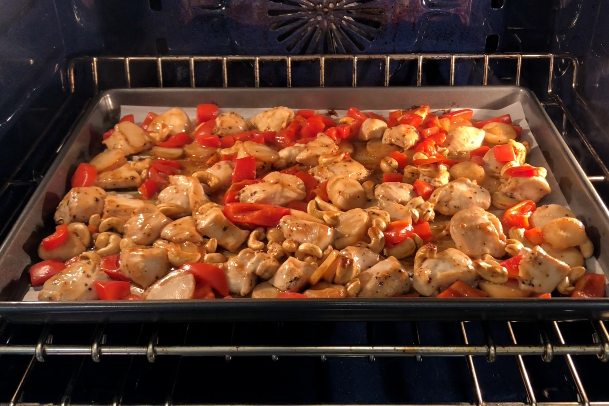 7. Spread chicken, pepper, water chestnuts and cashews evenly on the sheet pan. Cook for 12 minutes. -