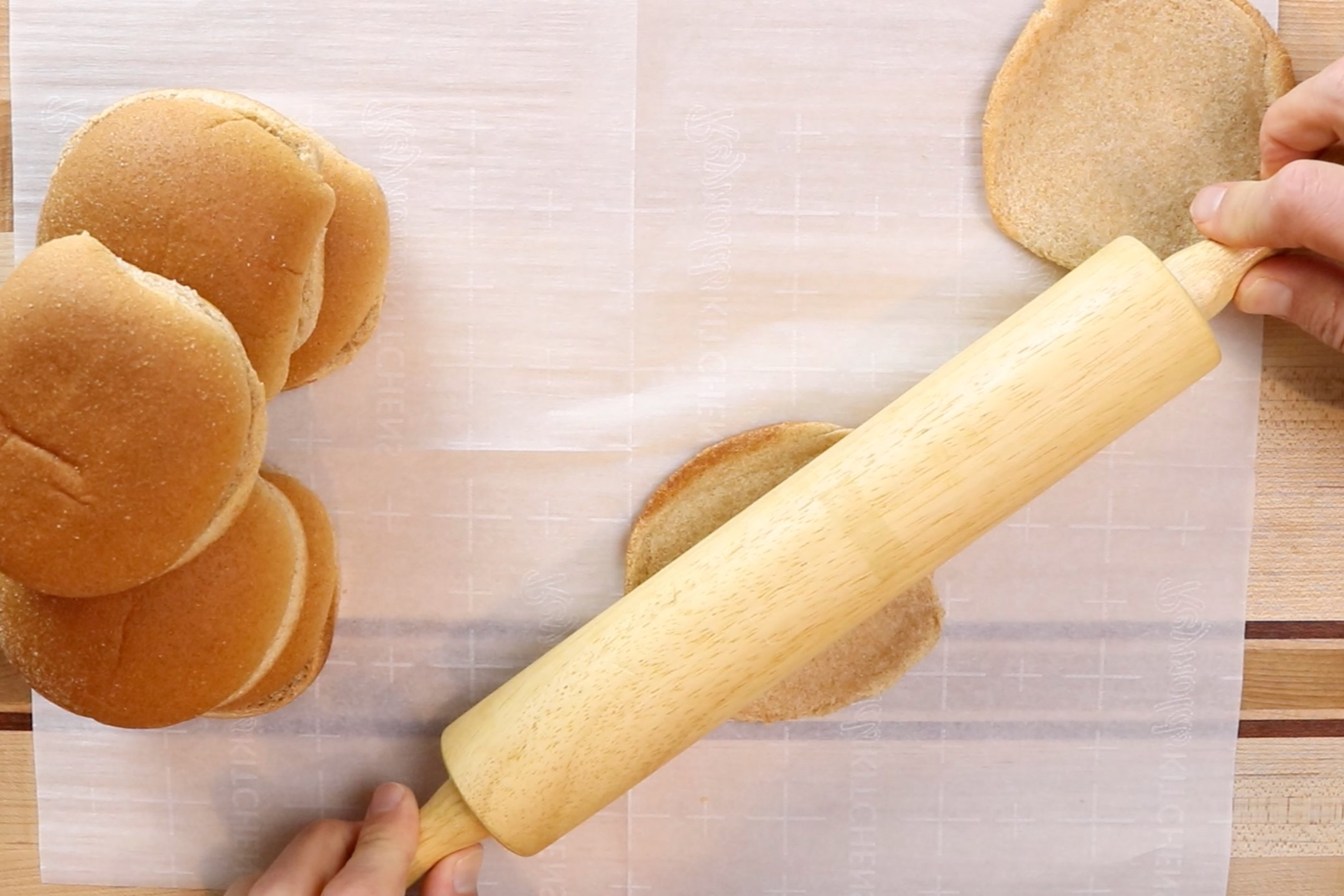 5. Using a rolling pin, flatten each burger bun half. -