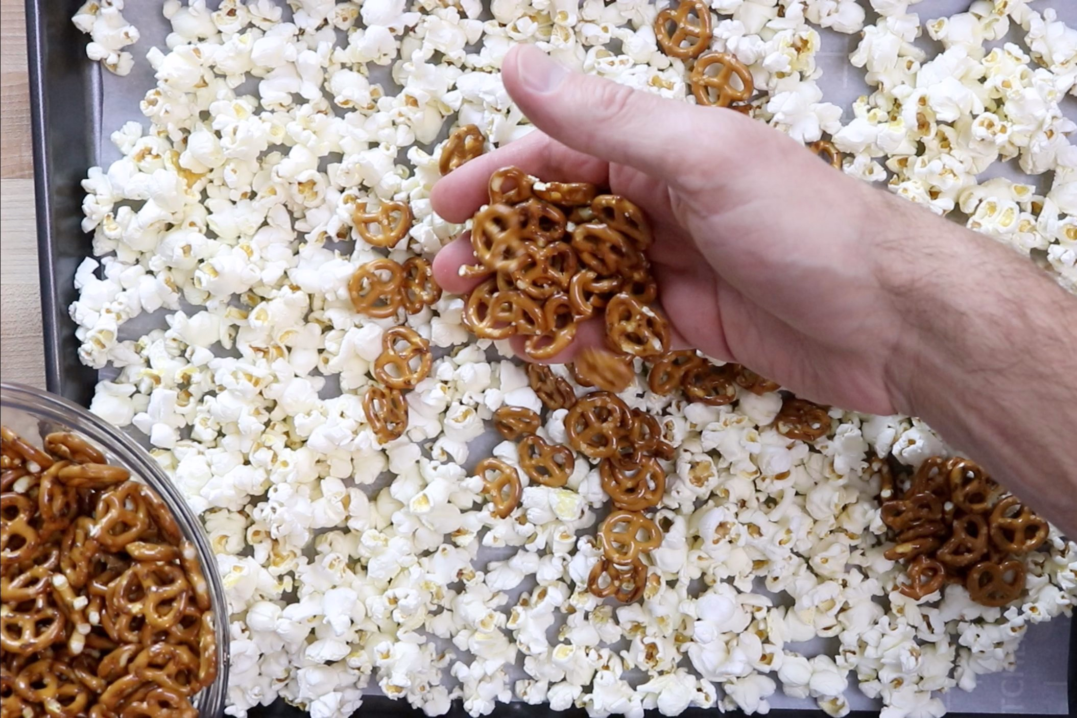 1. Make popcorn. Spread half of the popcorn and pretzels on one of two parchment lined (or Silpat lined) baking sheets. Set aside. -