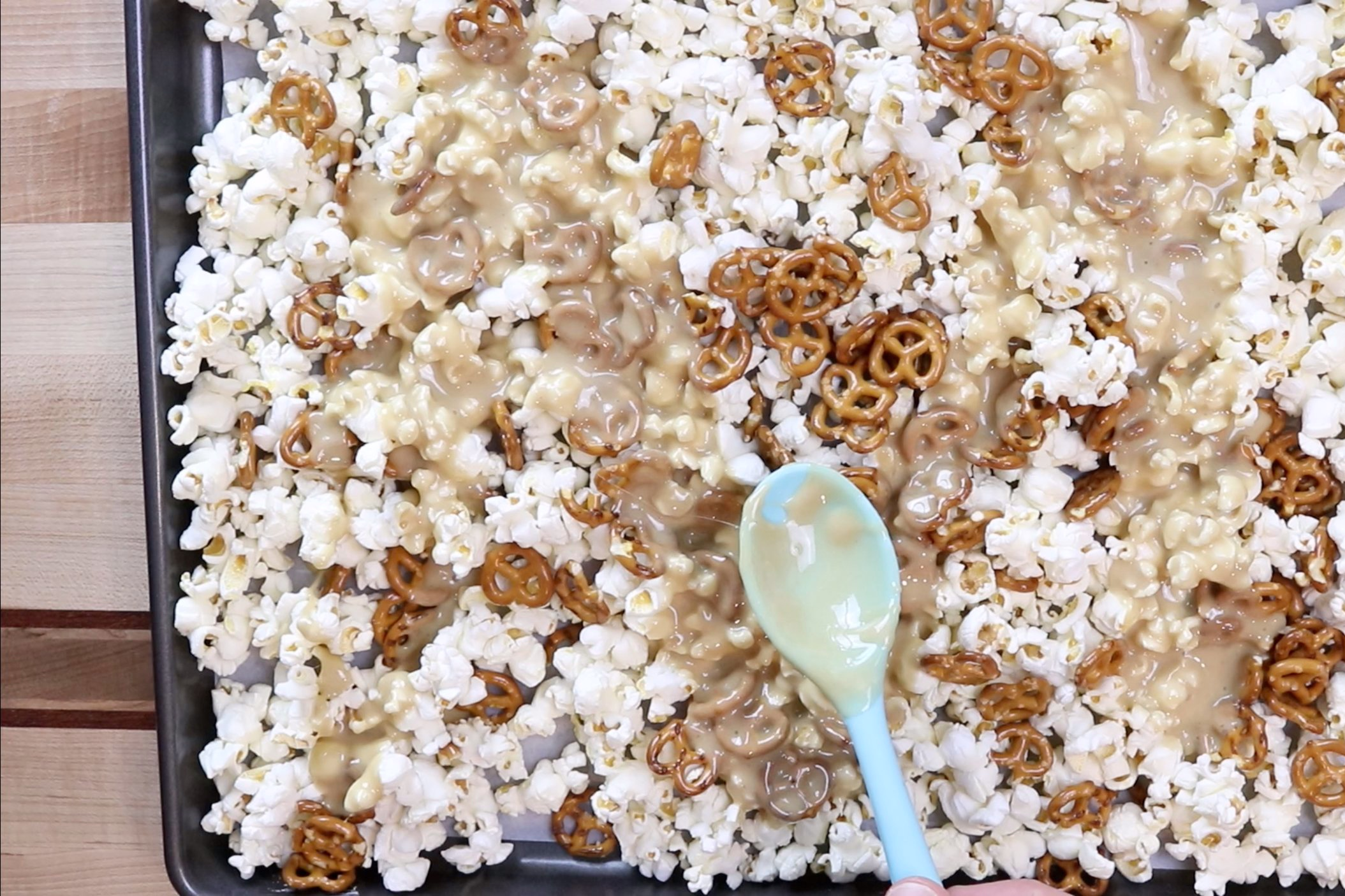 5. Pour the marshmallow mixture evenly between both baking sheets and stir until all the popcorn and pretzels are coated. -