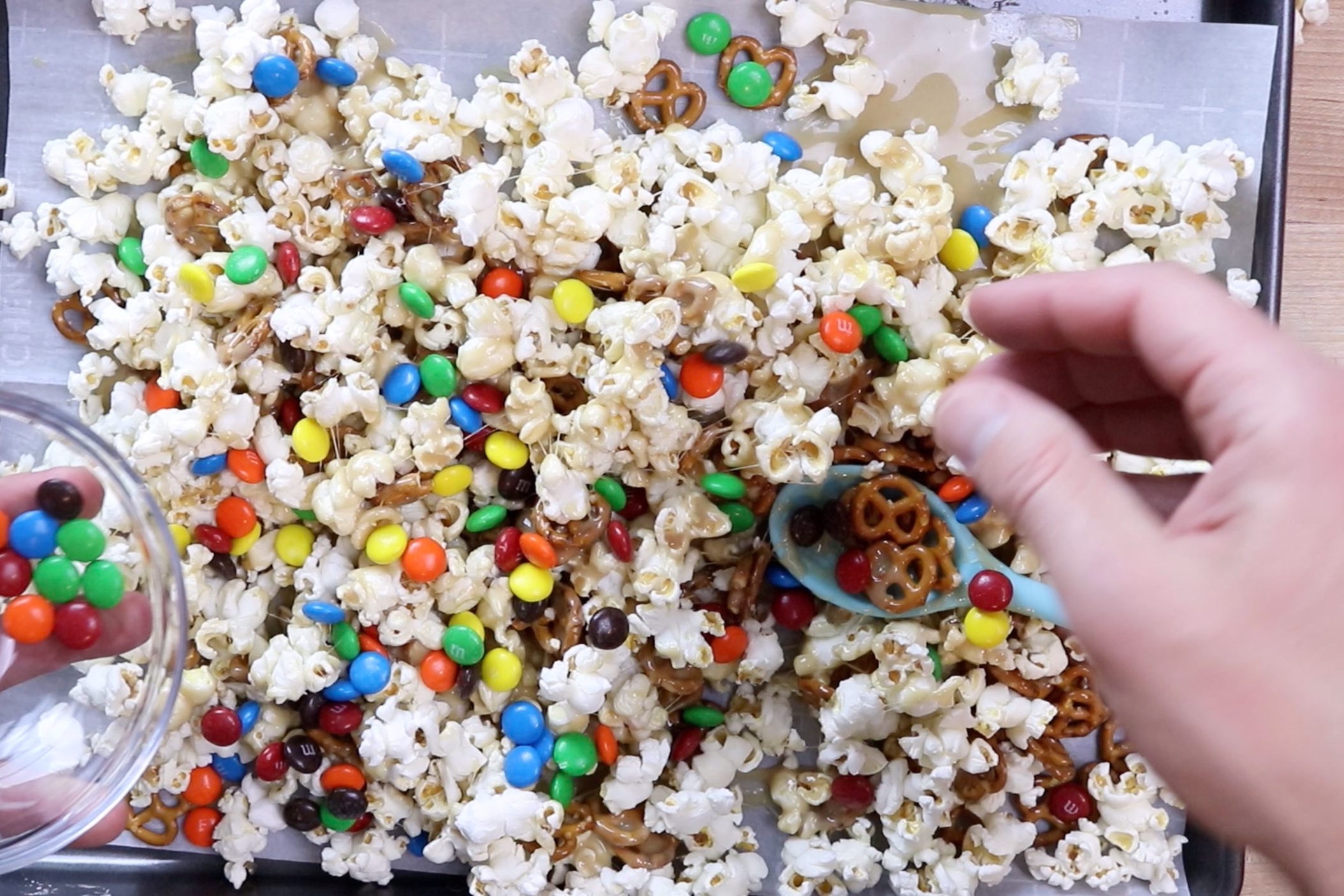 6. Add M&Ms and continue to stir. You can use your hands if needed. Just spray your hands with cooking spray and gently fold the popcorn mixture until all M&Ms are distributed evenly. -