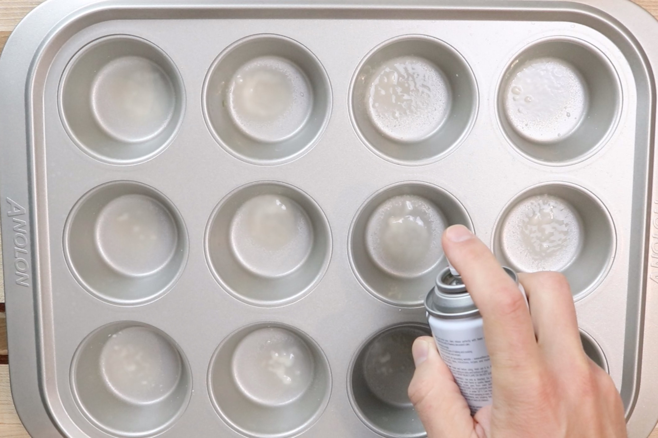 1. Preheat the oven to 350 degrees and spray a 12-cup muffin tin with baking spray. Pour some sugar in a bowl and set aside for rolling. -