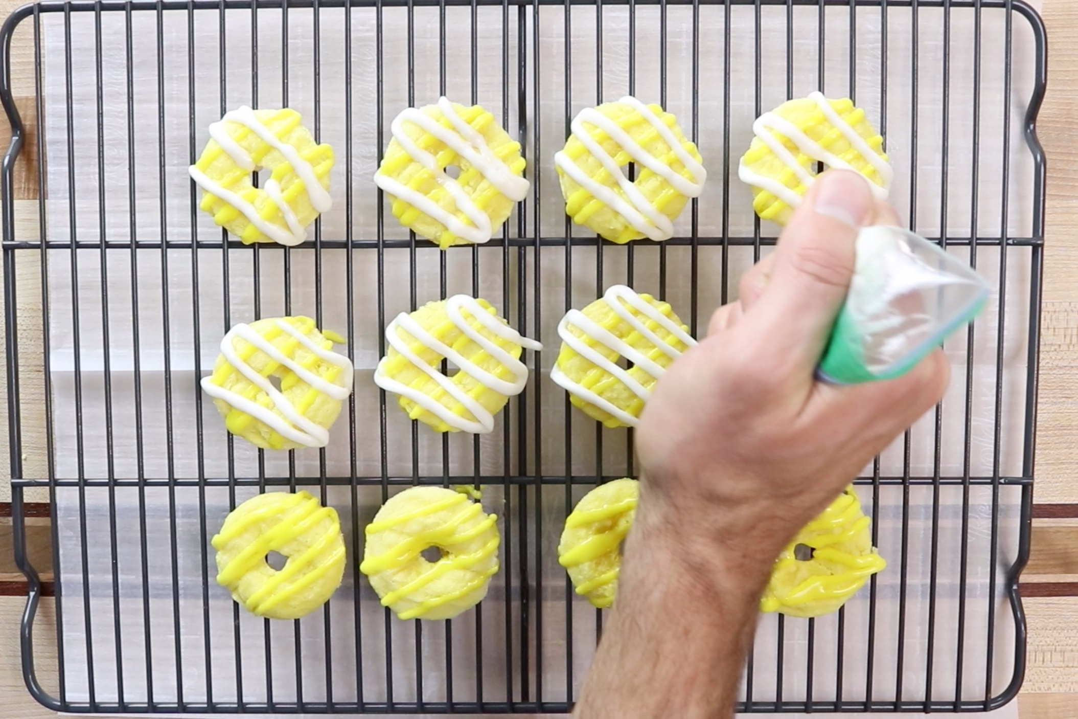 15. Cut a tiny hole in the corner of each bag of glaze. Drizzle each cookie with the white glaze and then with the yellow glaze alternating directions. -