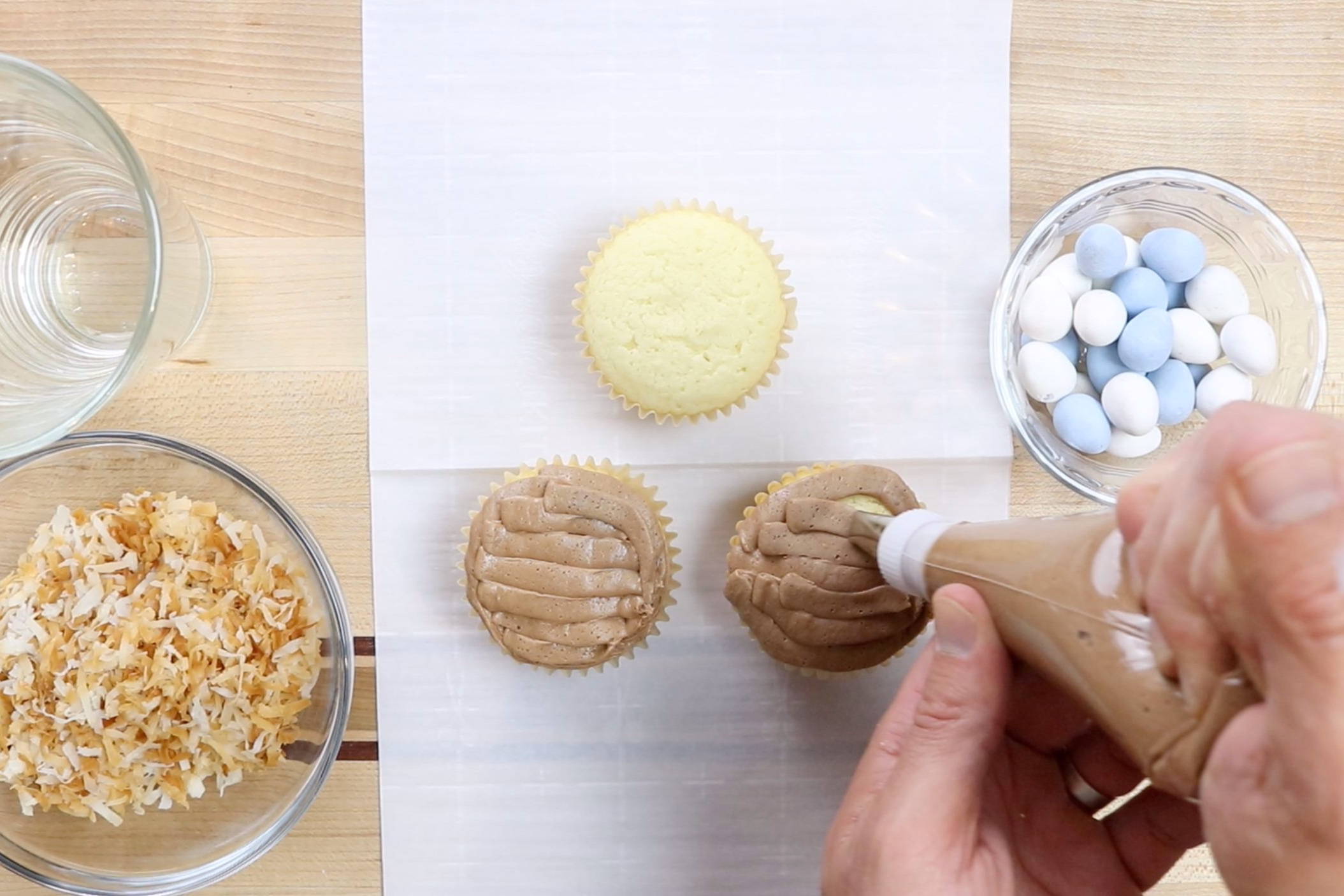 3. Using a knife or an icing bag, frost cooled cupcakes with chocolate buttercream frosting. -