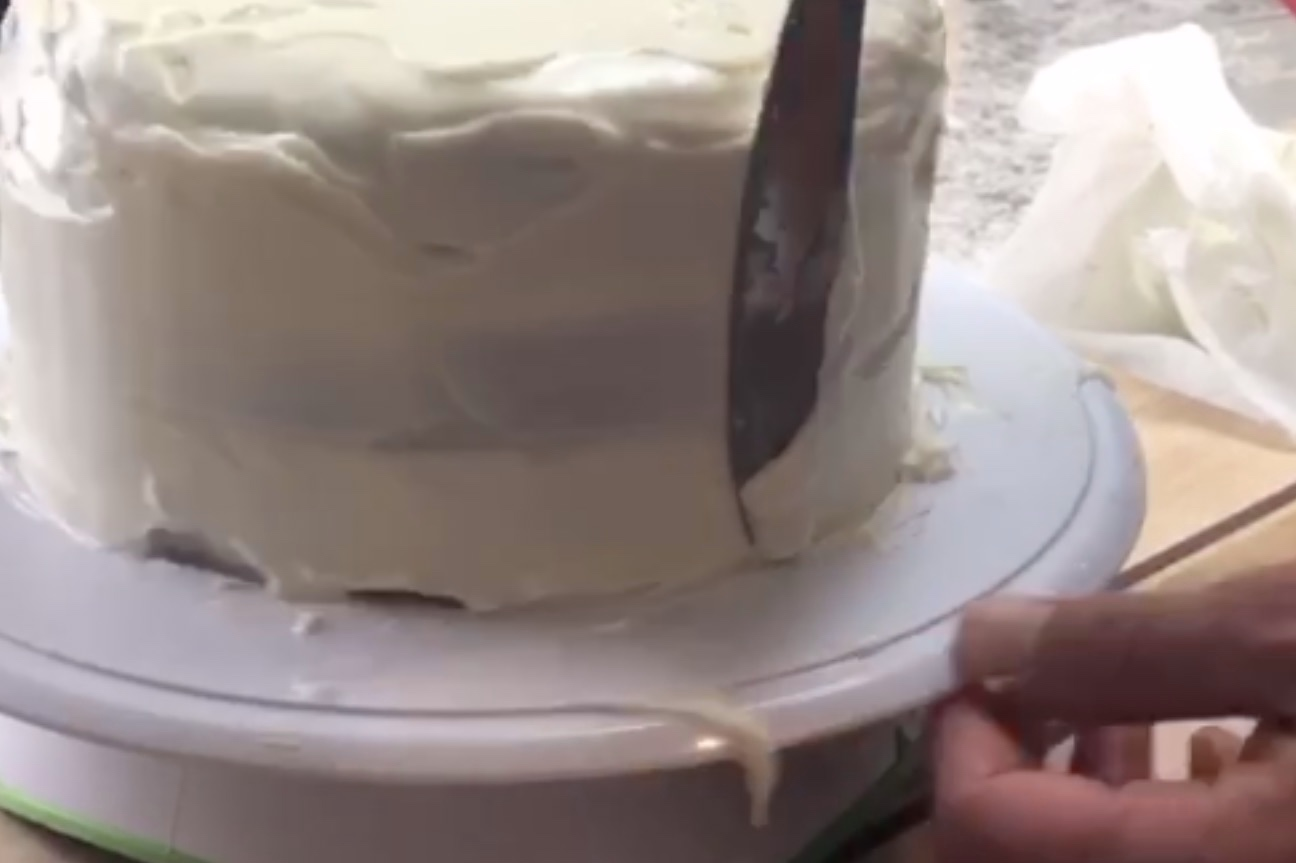 3. Spread the frosting along the sides of the cake smoothing the edges with a knife or a spatula until the entire cake is covered. -