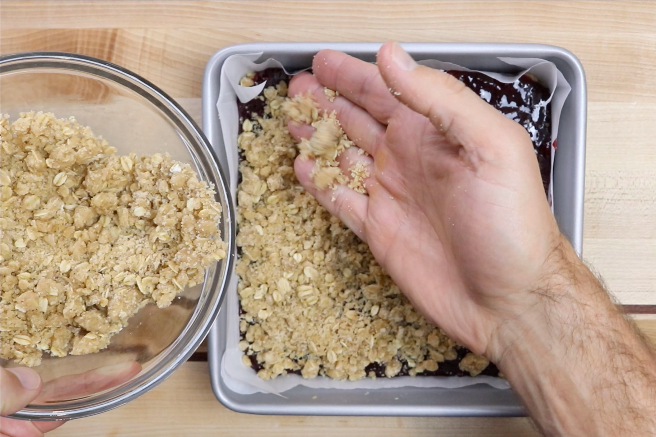 5. Remove from oven. Spread the raspberry jam over the crust and Sprinkle with remaining crumble. -