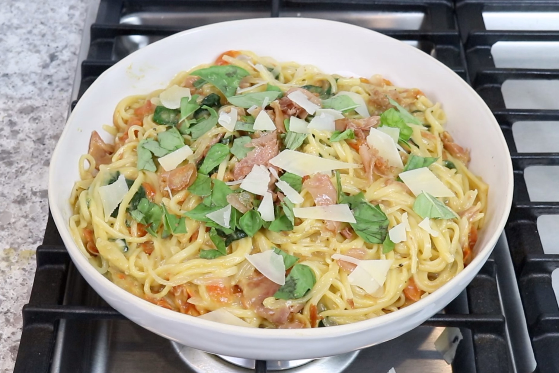6. Remove from heat and stir in crumbled prosciutto. Top with basil and Parmesan. Serve immediately. -