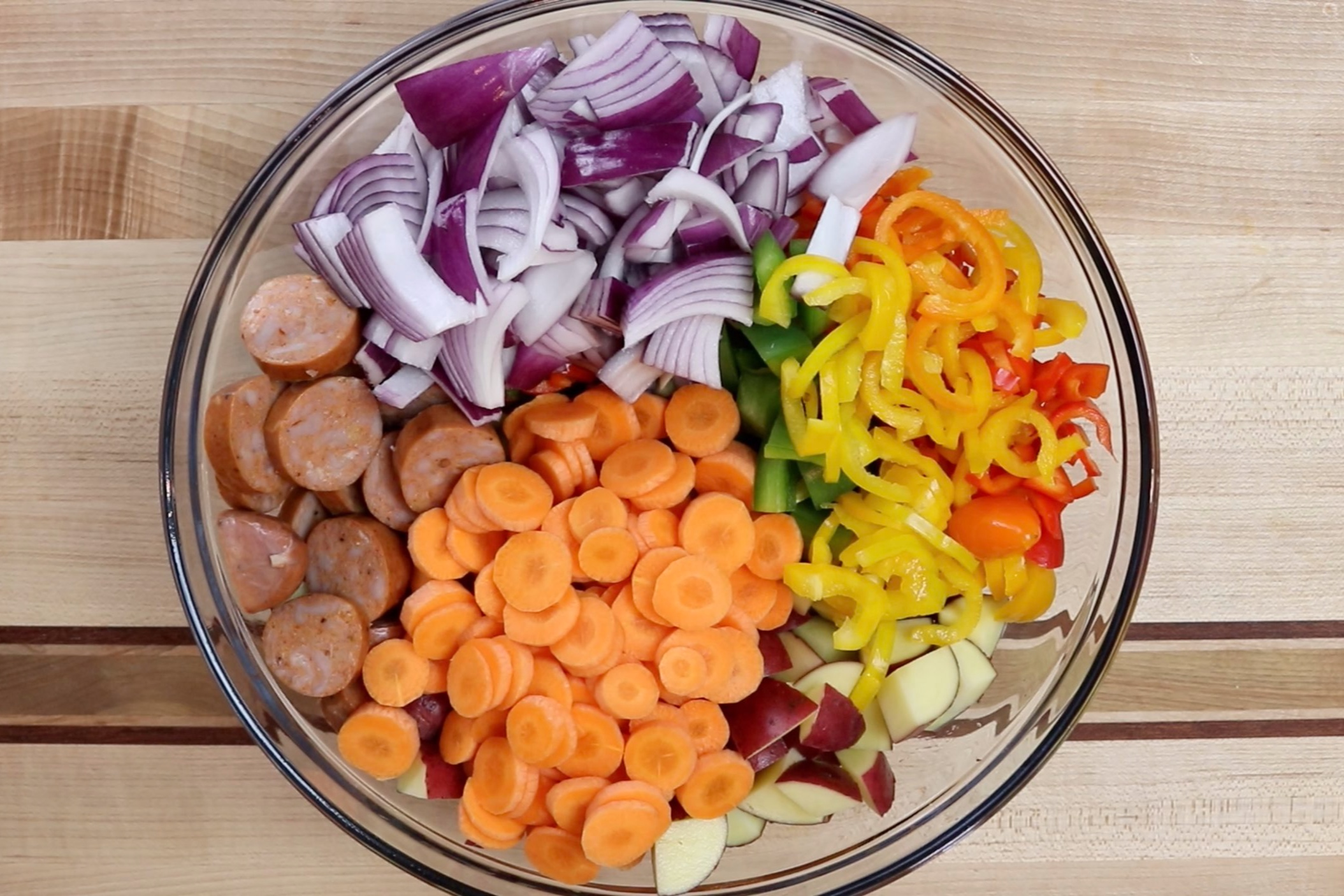 3. Cut the chicken sausage into 1-inch pieces, cut potatoes into small cubes, cut red onion into small wedges, cut the carrots into 1/2 inch pieces, chop the green pepper and slice the baby peppers into small rings. -