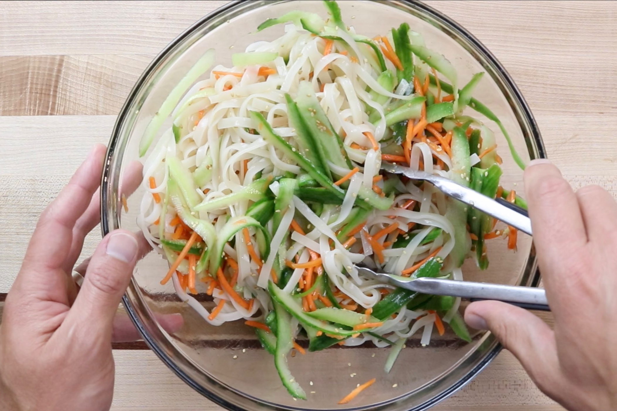 8. In a large serving bowl, toss the noodles, carrots, and cucumbers with the dressing. -