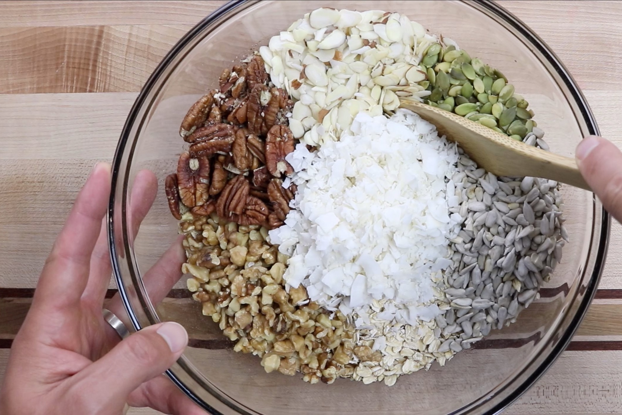 3. Add the oats, walnuts, pecans, almonds, pepitas, sunflower seeds and coconut flakes. Fold mixture until all pieces are lightly coated. -