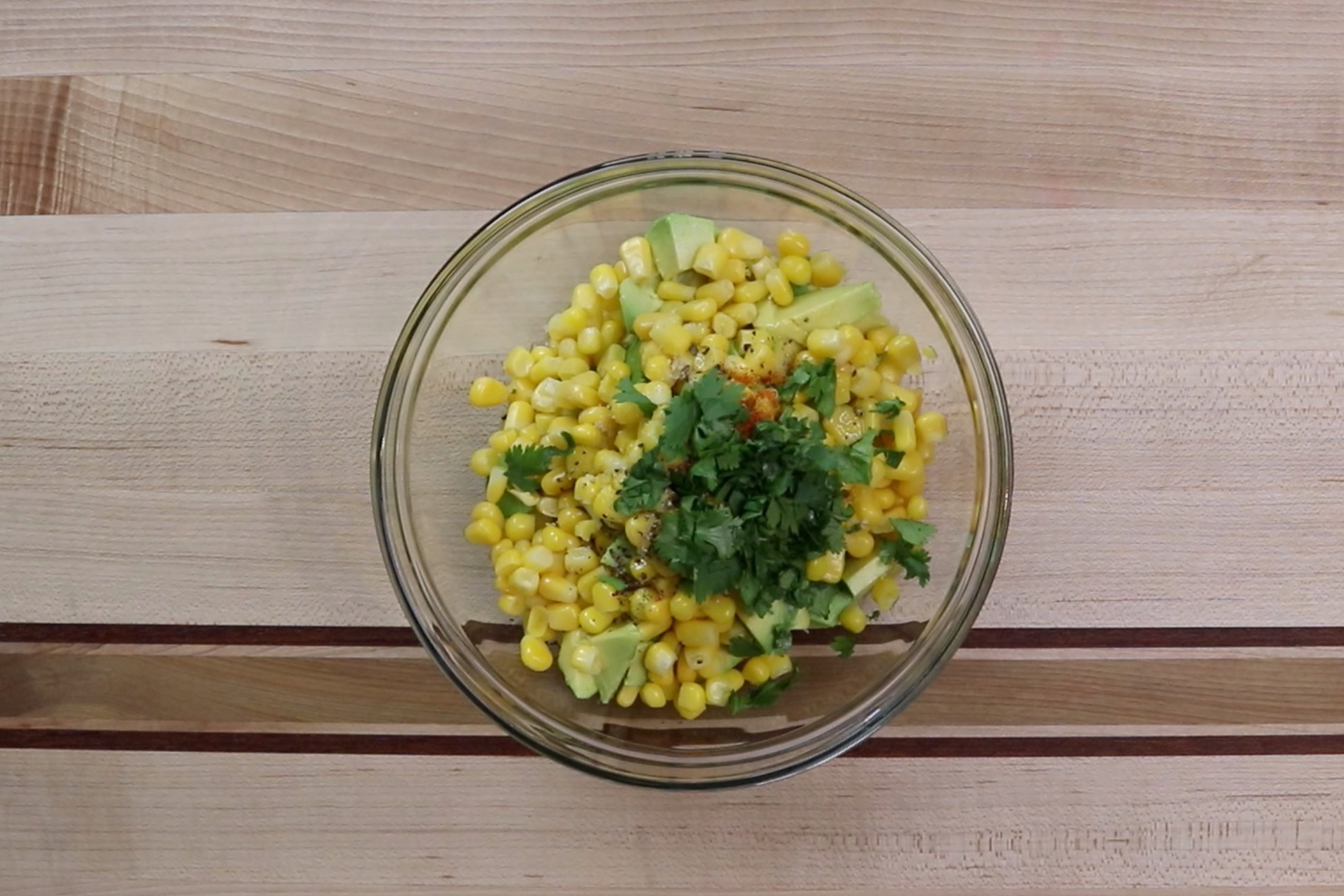 1. In a medium bowl add the avocados, corn, olive oil, lime juice, salt, black pepper, cayenne and cilantro. -