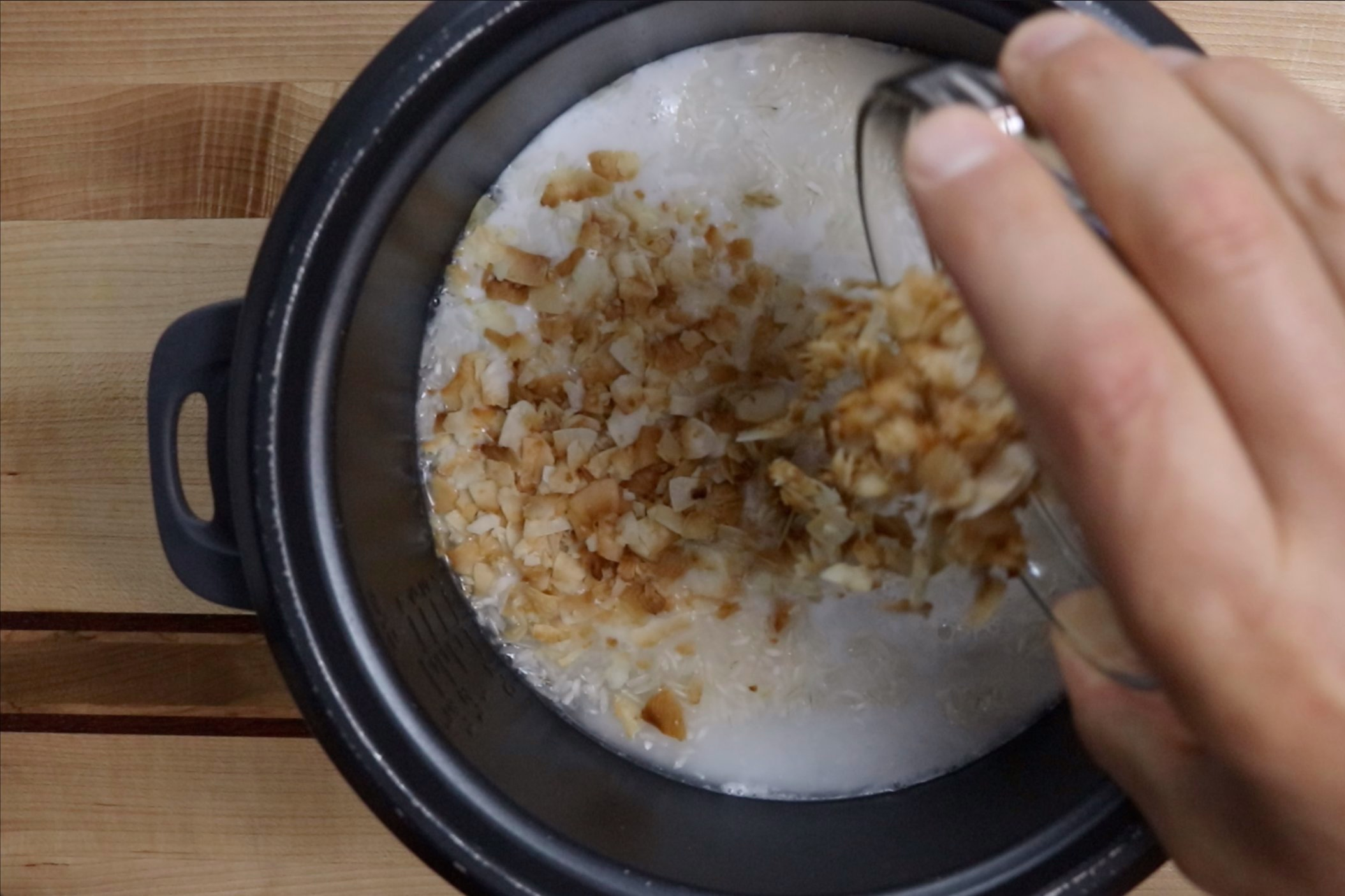 1. In a rice cooker, add the rice, coconut milk, pineapple juice, water, salt and toasted coconut. -