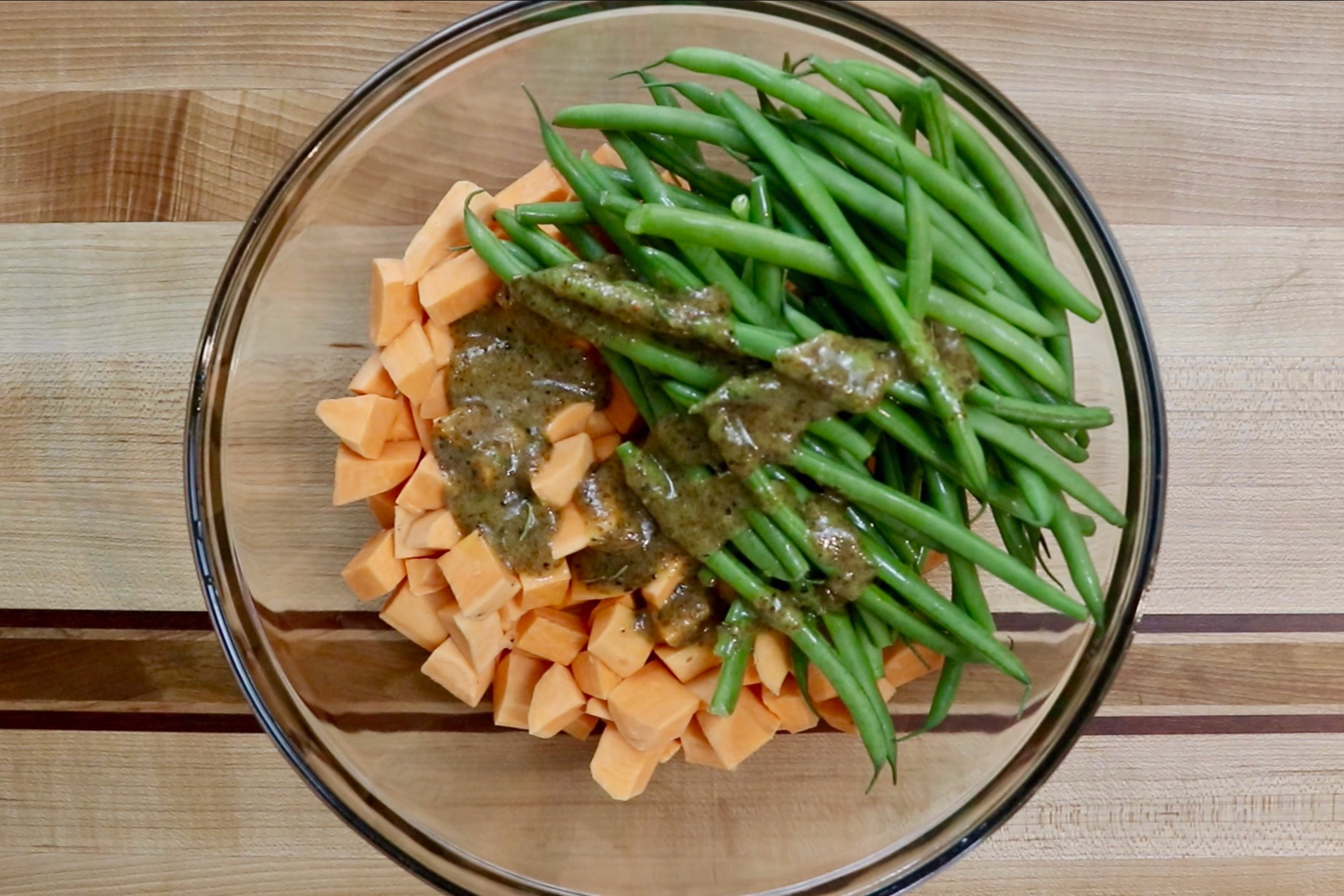 4. In a large bowl, add the sweet potatoes, green beans, olive oil and reserved marinade. Stir until all pieces are coated. -