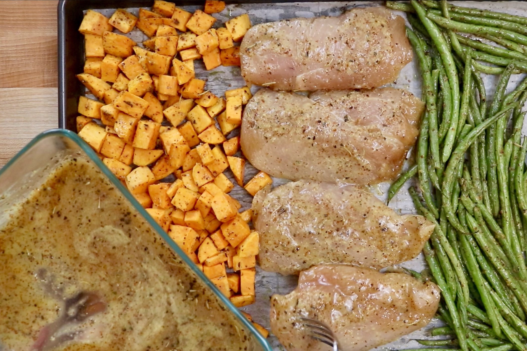7. Remove baking sheet from oven, move the veggies to the side and add the chicken spaced evenly apart. Brush remaining marinade over the chicken. Cook for another 12-15 minutes or until chicken is cooked through and veggies are tender. -