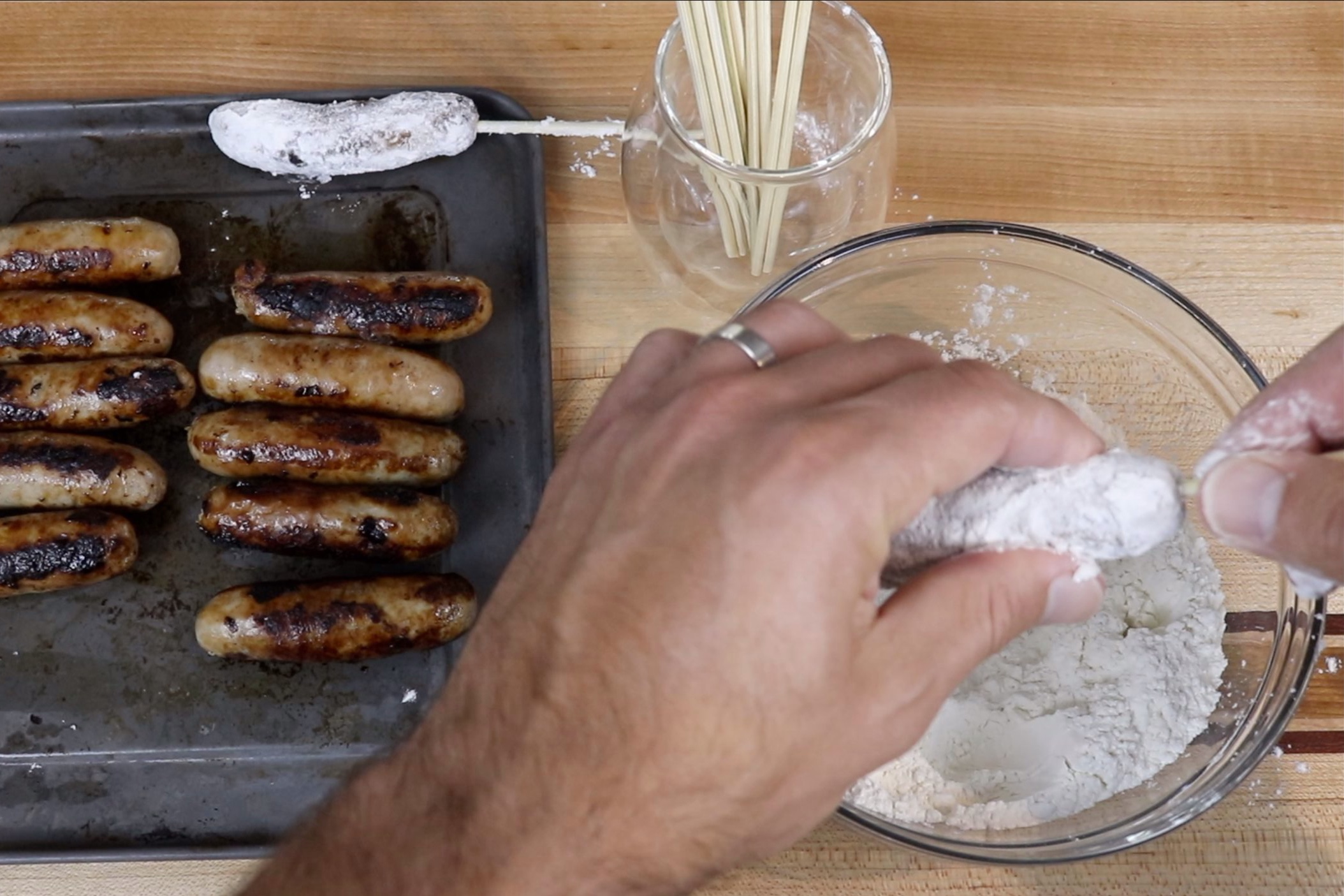 4. Once sausages are cool enough to handle, dredge each link in flour and skewer each sausage lengthwise with a wooden stick. Set aside. -