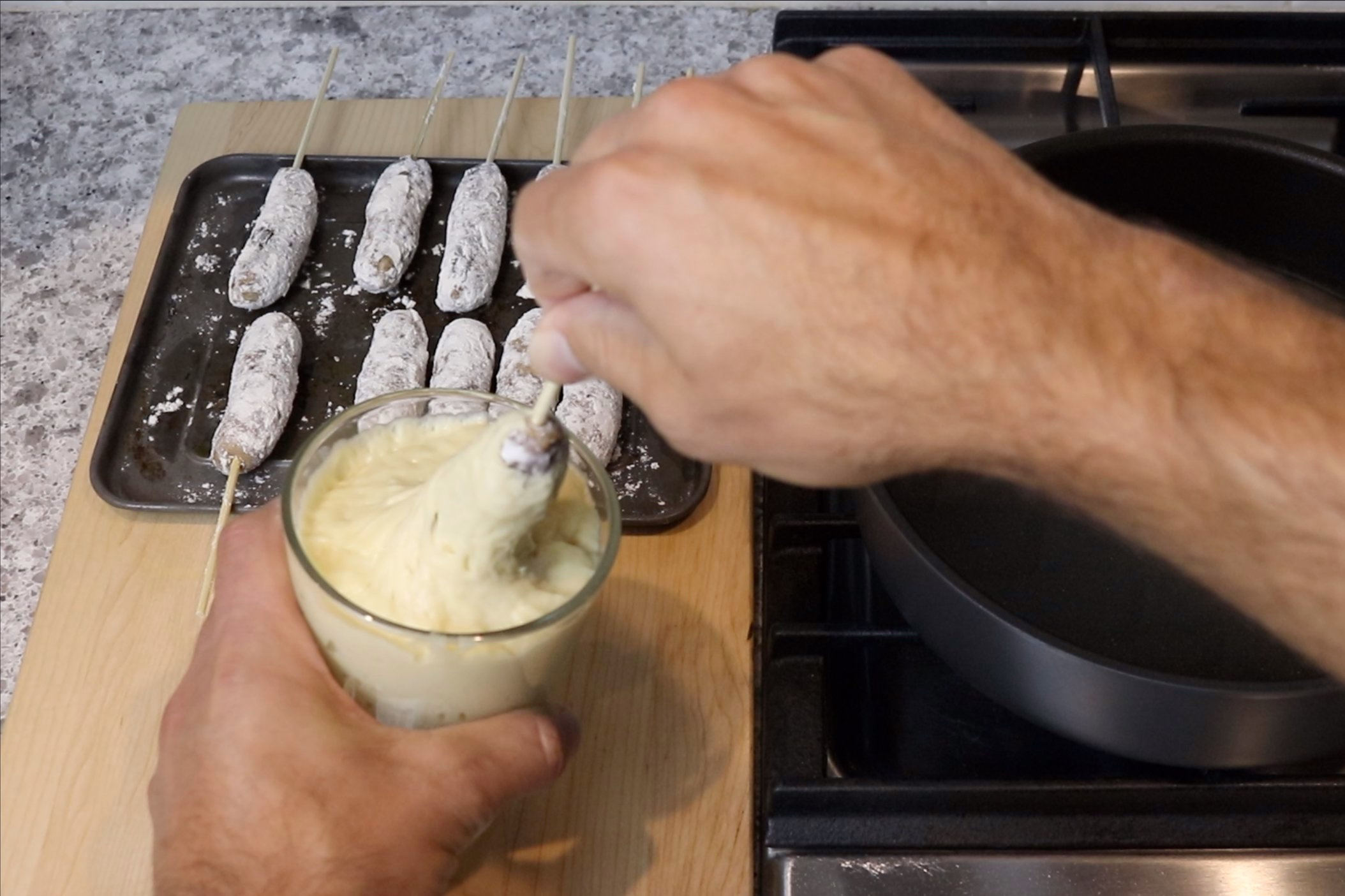 9. Dip the skewered sausages in pancake batter, spinning the skewer until the sausage is lightly coated. -