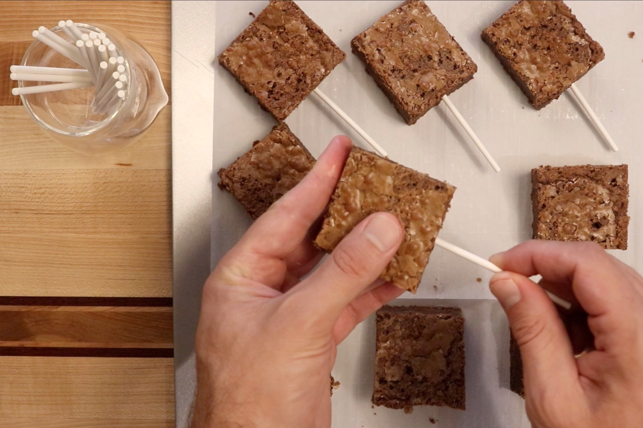 11. Gently insert a lollipop stick into the end of each brownie square. -