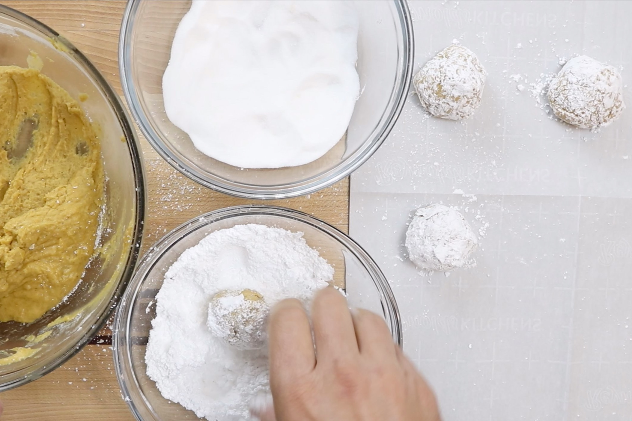 11. Then drop the ball in the powdered sugar and coat completely. Place dough ball onto baking sheet a couple of inches apart. Repeat steps making all the dough balls. -