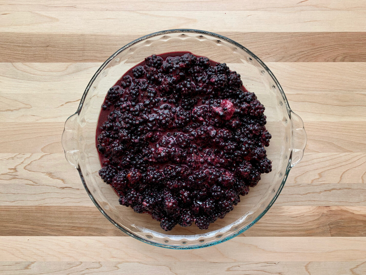 5. Pour blackberry mixture into greased pie pan and spread berries evenly. -