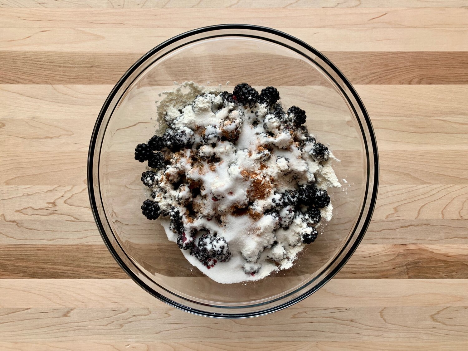 2. Add blackberries to a large bowl. Sprinkle blackberries with sugar, flour, cornstarch, and cinnamon. Gently stir until fully combined. Let sit for 5 minutes. -