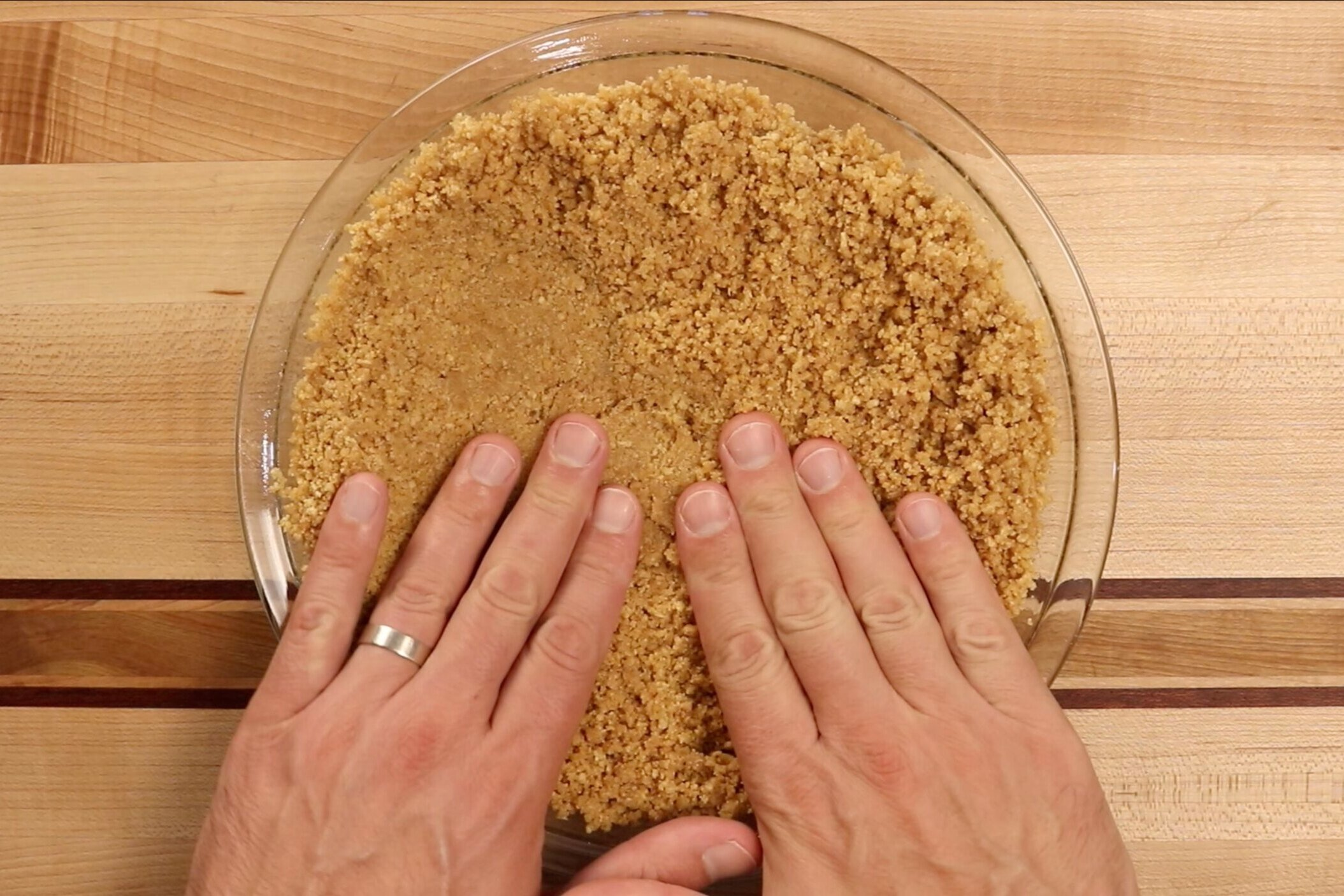 4.  Pour the graham cracker mixture into the pie plate. Press the graham cracker up the sides and on the bottom until the pie plate is covered evenly. -