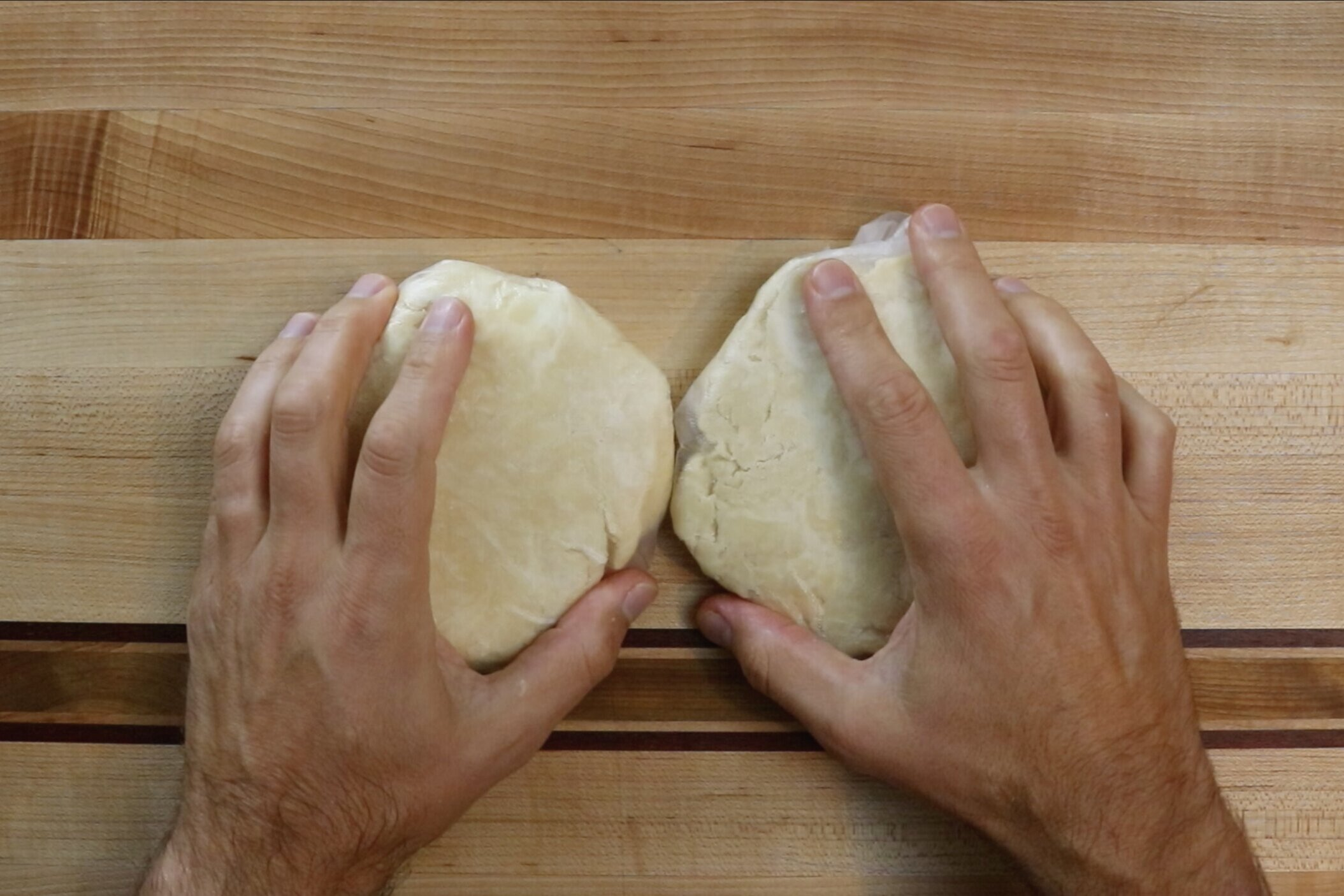 4. Finish by kneading the dough on a floured surface with your hands until you form a large ball. Divide the pie dough in half and flatten the balls into a discs. Wrap in plastic wrap and chill in refrigerator for 2 hours. -