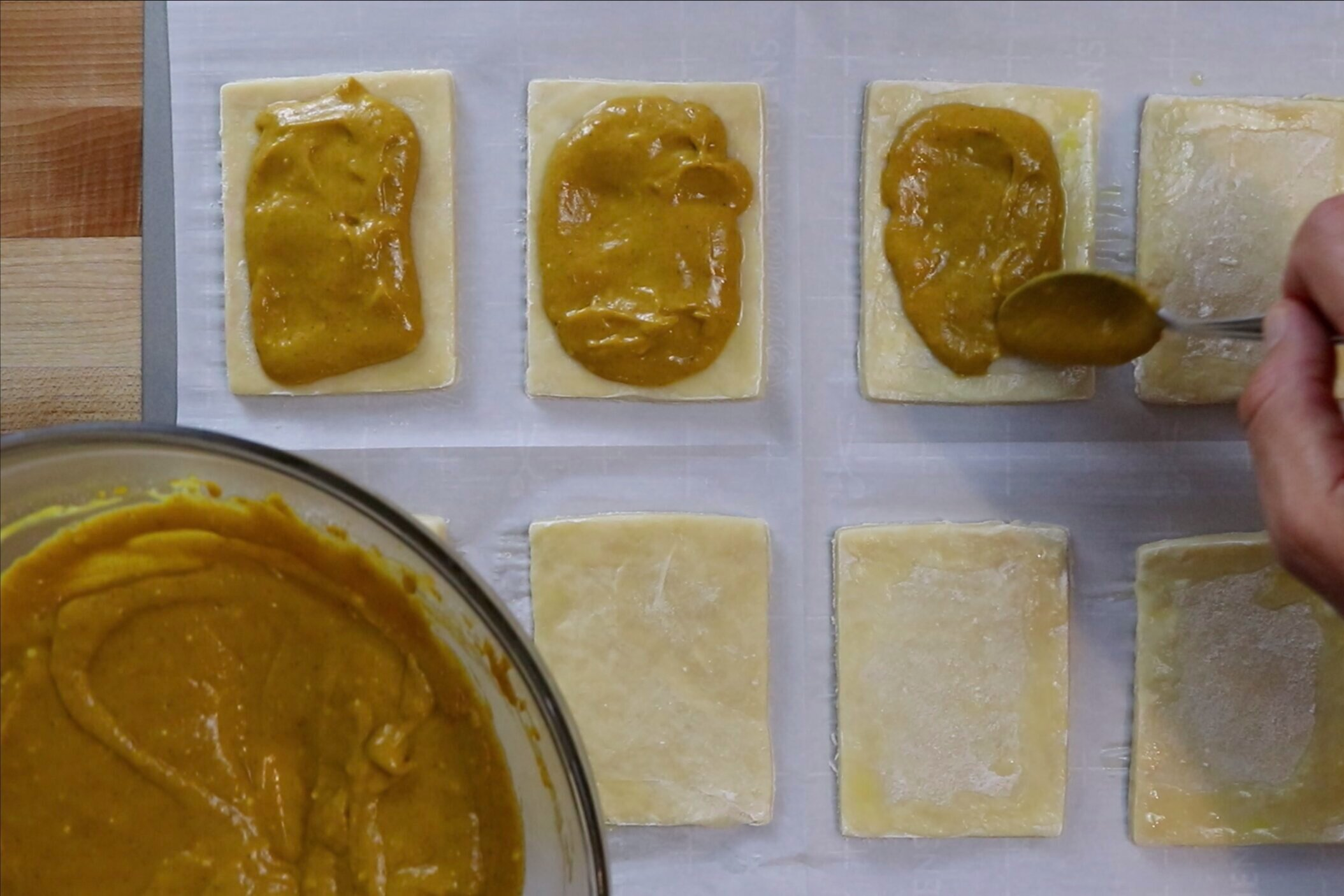 6. Scoop around 2 tablespoons of the pumpkin filling in the middle of each rectangle. Spread pumpkin evenly leaving space around the border. -
