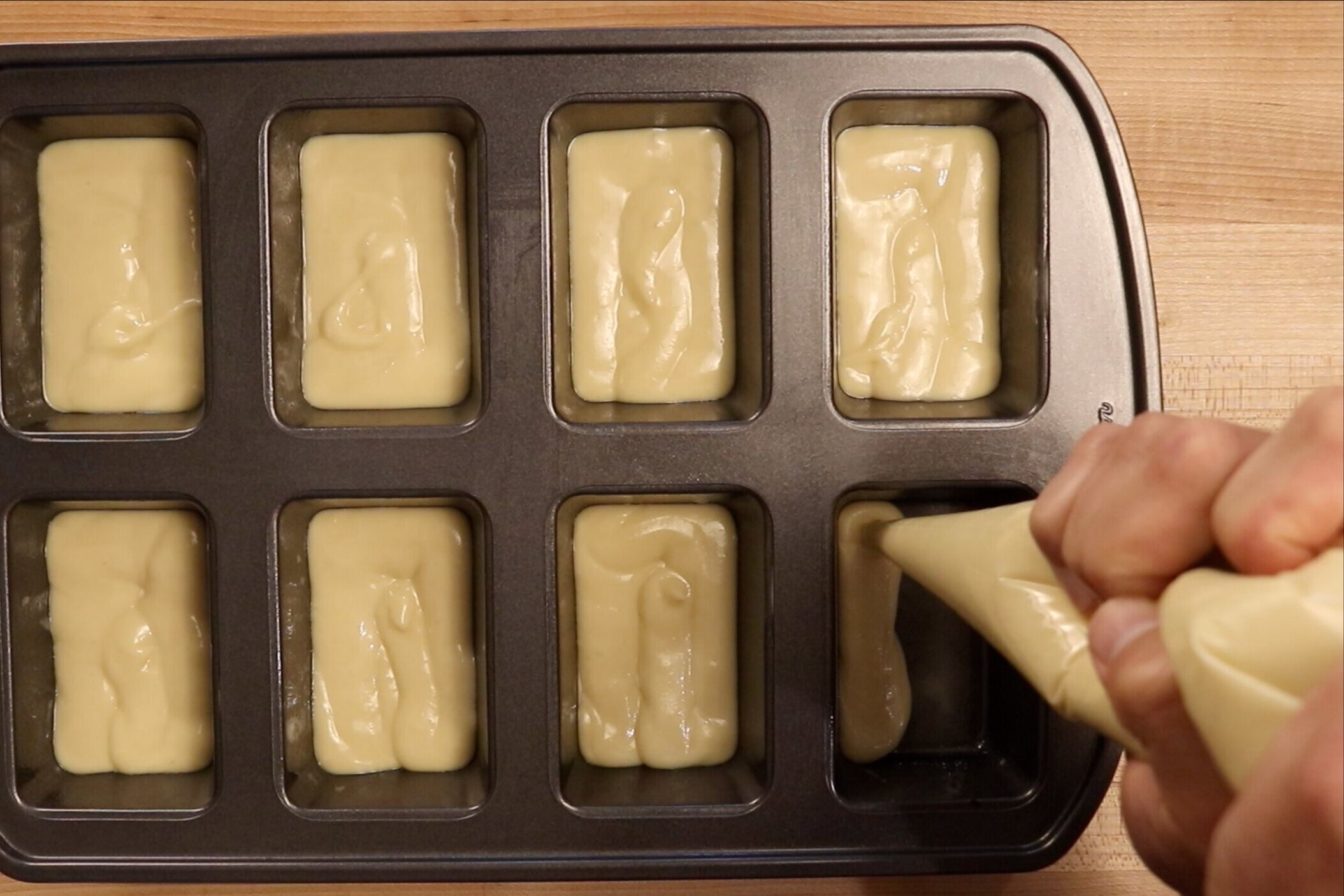 10. Spoon or pipe half of the batter into the greased mini-loaf pan filling. -